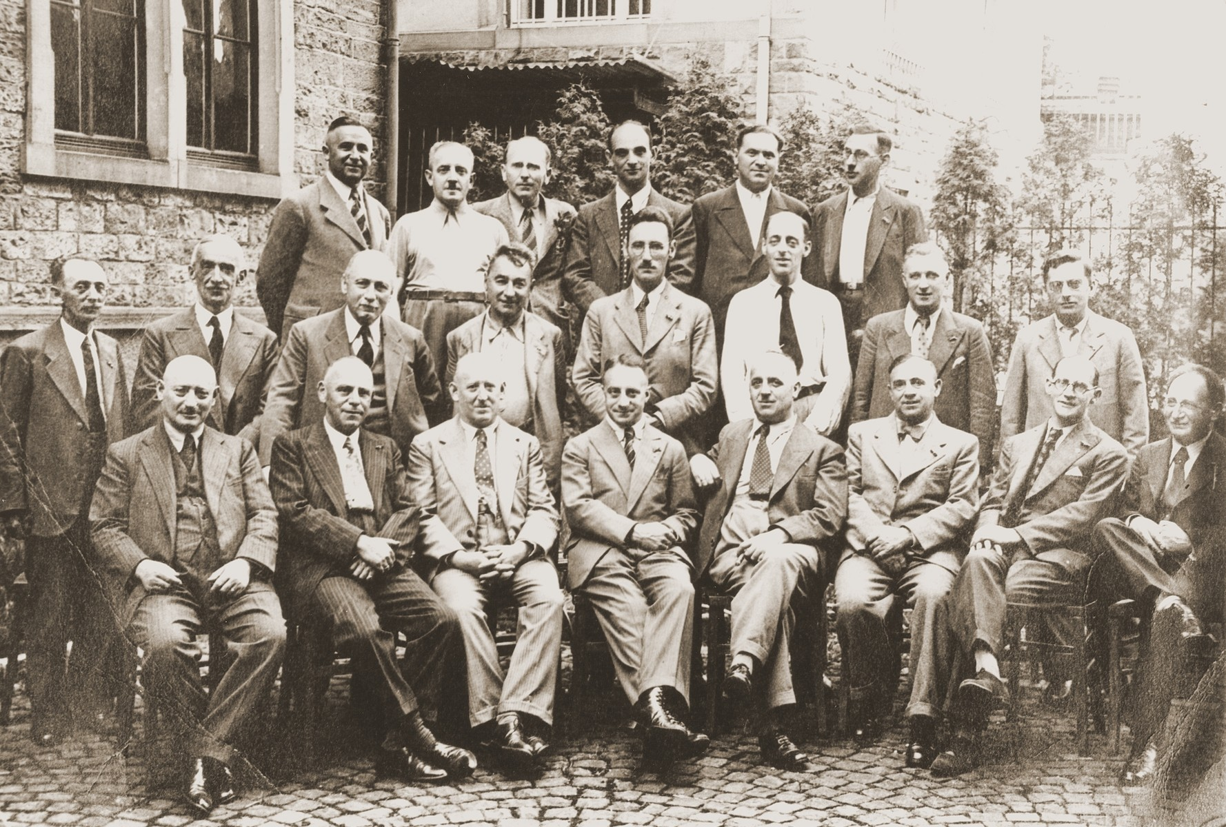 Group portrait of twenty-two members of the congregation of the liberal Zerrennerstrasse synagogue.    Only ten of these men are known to have survived, most by emigration.  Pictured in the first row, left to right: Jakob Bensinger, Leo Erlanger, Salomon Bensinger, Adolf Weill, Leopold Blum, Max Hichberger, Max Lieben, and Alexander Levisohn.  Second row, left to right: Nathan Heitlinger, David Peritz, Helmut Wolff, Alfred Landau, Prof. Dr. Simon Bloch, Prof. Dr. Ascher Fritzmartin, Walter Wolff, and Fritz Gottschalk.  Third row, left to right:  Philipp Braun, Emil Simon, [?] Dreyfus, Leopold Blum, Leo Klein, and David Levy.