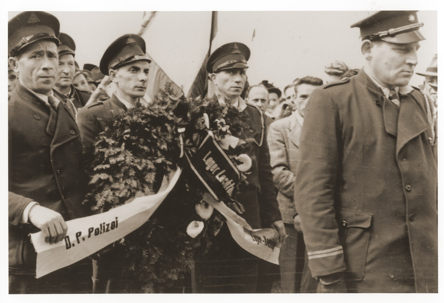 DP police from the Lechfeld displaced persons camp carry a wreath to the site of a memorial to Jewish victims at the Dachau concentration camp.