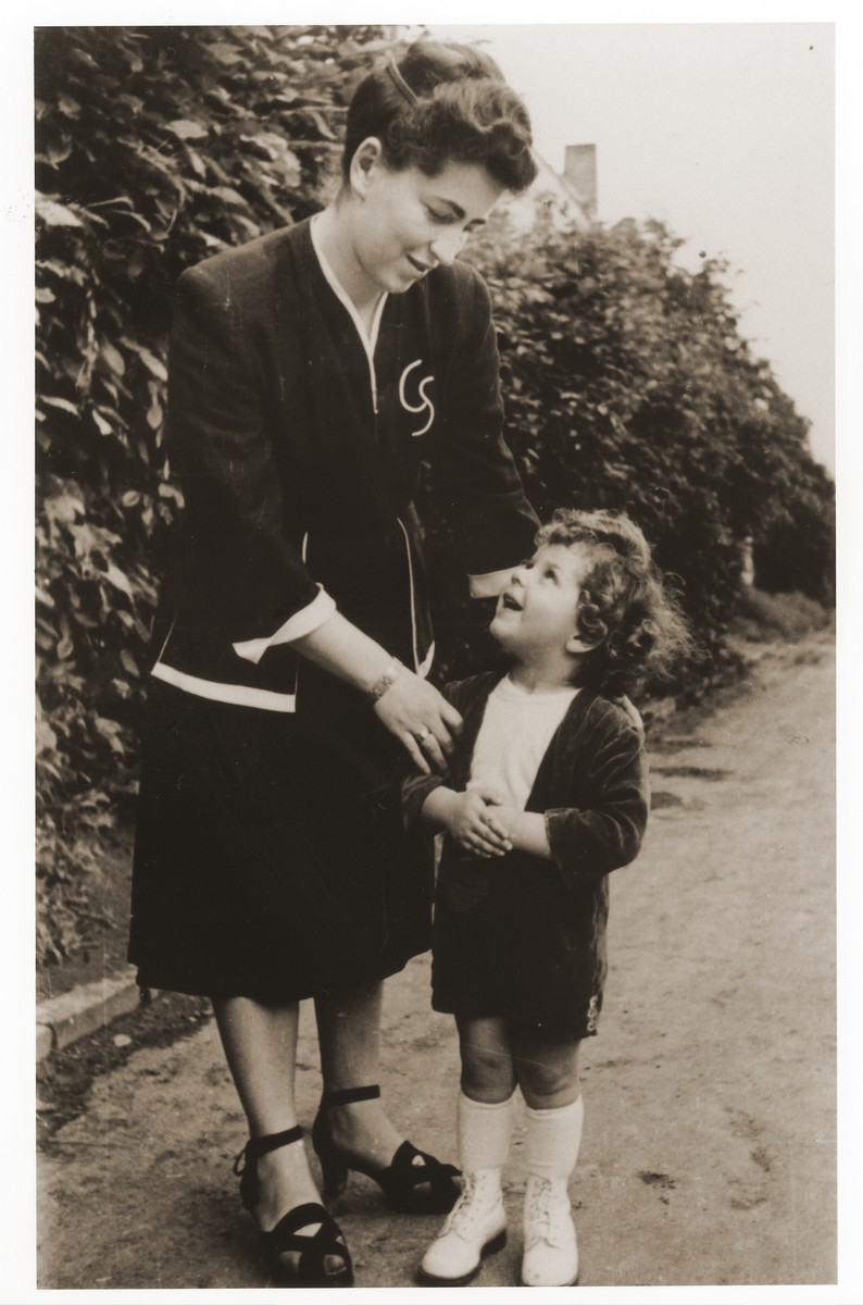 Mrs. Kolanchik talks to her son in the Lechfeld displaced persons camp.  Gerzon Trzcina was born in Krasnosielc, Poland in 1922.  He was the son of Dina Kassel and Benam Yitzhak, who was a businessman in the leather trade.  Gerzon had one older brother, Jacob, and two sisters, Faiga (b. 1918) and Perl (b. 1920).  When the war broke out, Gerzon was working as a photographer's assistant (among other jobs) in Warsaw.  Following the German invasion of September, 1939, Gerzon was slightly wounded by shrapnel.  Soon after, a drunken German soldier, forcibly cut Gerzon's hair.  When the soldier made him stoop down to pick up the cuttings, Gerzon grabbed the German's gun and ran away.  After a short time in hiding, Gerzon returned to his hometown, where he learned that eighty Jews had been murdered in the synagogue during the first week of the war in one of the first large-scale atrocities against Polish Jews.  Among those killed was Gerzon's eighty-two-year-old grandfather, Haskel Kassel.  Gerzon moved on to Makow Mazowiecki, where he was forced to clean the stables the Germans had set up in the town's synagogue.  In the late fall, Gerzon escaped with his family to Bialystok, where he worked in a tannery until the family was deported to the Soviet interior in June, 1940.  Along with a group of Polish and Jewish refugees, the Trzcinas were sent to the Kiltovo labor camp in northern Russia.  Harsh conditions and poor nutrition led to Gerzon's father's death in the camp.  The family remained in Kiltovo until the German invasion of the Soviet Union in June of 1941.  Soon after, the refugees were allowed to leave the camp, and the Trzcinas moved to nearby Syktyvkar (capital of the Komi republic), where Gerzon worked in a construction company and later in a tannery.  In Syktyvkar, Gerzon was reunited with Gittel Blankitner, a Jewish refugee from Mlawa, whom he had met earlier in his travels in the Soviet Union.  (Gittel's father perished in Aushwitz, and her mother and siblings were killed in Treblinka.) In November, 1944, Gerzon and Gittel were married. The couple left the Soviet Union with their new baby in 1946.  Returning for a brief time to Poland, the family soon joined the wave of survivors streaming toward the Western zones of occupation.  After their arrival in Germany, the Trzcinas stayed in several DP camps including Vilseck, Wurzburg and Lechfeld, where Gerzon worked as an UNRRA photographer.  In March 1951, the family immigrated to the United States.