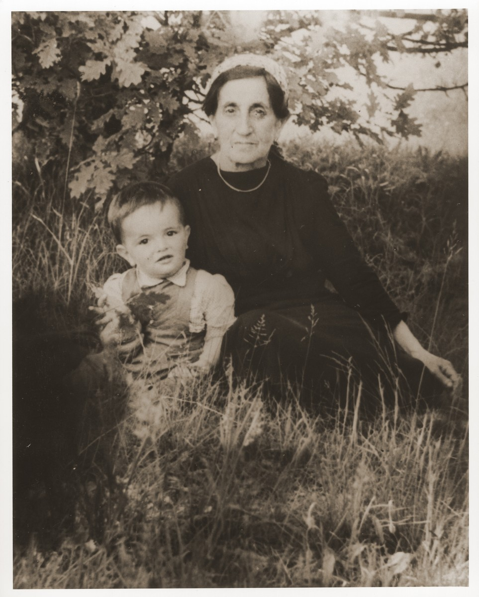 Dina Kassel Trzcina sits in the grass with her grandson, Benjamin, at the Vilseck displaced persons camp.  Gerzon Trzcina was born in Krasnosielc, Poland in 1922.  He was the son of Dina Kassel and Benam Yitzhak, who was a businessman in the leather trade.  Gerzon had one older brother, Jacob, and two sisters, Faiga (b. 1918) and Perl (b. 1920).  When the war broke out, Gerzon was working as a photographer's assistant (among other jobs) in Warsaw.  Following the German invasion of September, 1939, Gerzon was slightly wounded by shrapnel.  Soon after, a drunken German soldier, forcibly cut Gerzon's hair.  When the soldier made him stoop down to pick up the cuttings, Gerzon grabbed the German's gun and ran away.  After a short time in hiding, Gerzon returned to his hometown, where he learned that eighty Jews had been murdered in the synagogue during the first week of the war in one of the first large-scale atrocities against Polish Jews.  Among those killed was Gerzon's eighty-two-year-old grandfather, Haskel Kassel.  Gerzon moved on to Makow Mazowiecki, where he was forced to clean the stables the Germans had set up in the town's synagogue.  In the late fall, Gerzon escaped with his family to Bialystok, where he worked in a tannery until the family was deported to the Soviet interior in June, 1940.  Along with a group of Polish and Jewish refugees, the Trzcinas were sent to the Kiltovo labor camp in northern Russia.  Harsh conditions and poor nutrition led to Gerzon's father's death in the camp.  The family remained in Kiltovo until the German invasion of the Soviet Union in June of 1941.  Soon after, the refugees were allowed to leave the camp, and the Trzcinas moved to nearby Syktyvkar (capital of the Komi republic), where Gerzon worked in a construction company and later in a tannery.  In Syktyvkar, Gerzon was reunited with Gittel Blankitner, a Jewish refugee from Mlawa, whom he had met earlier in his travels in the Soviet Union.  (Gittel's father perished in Aush
