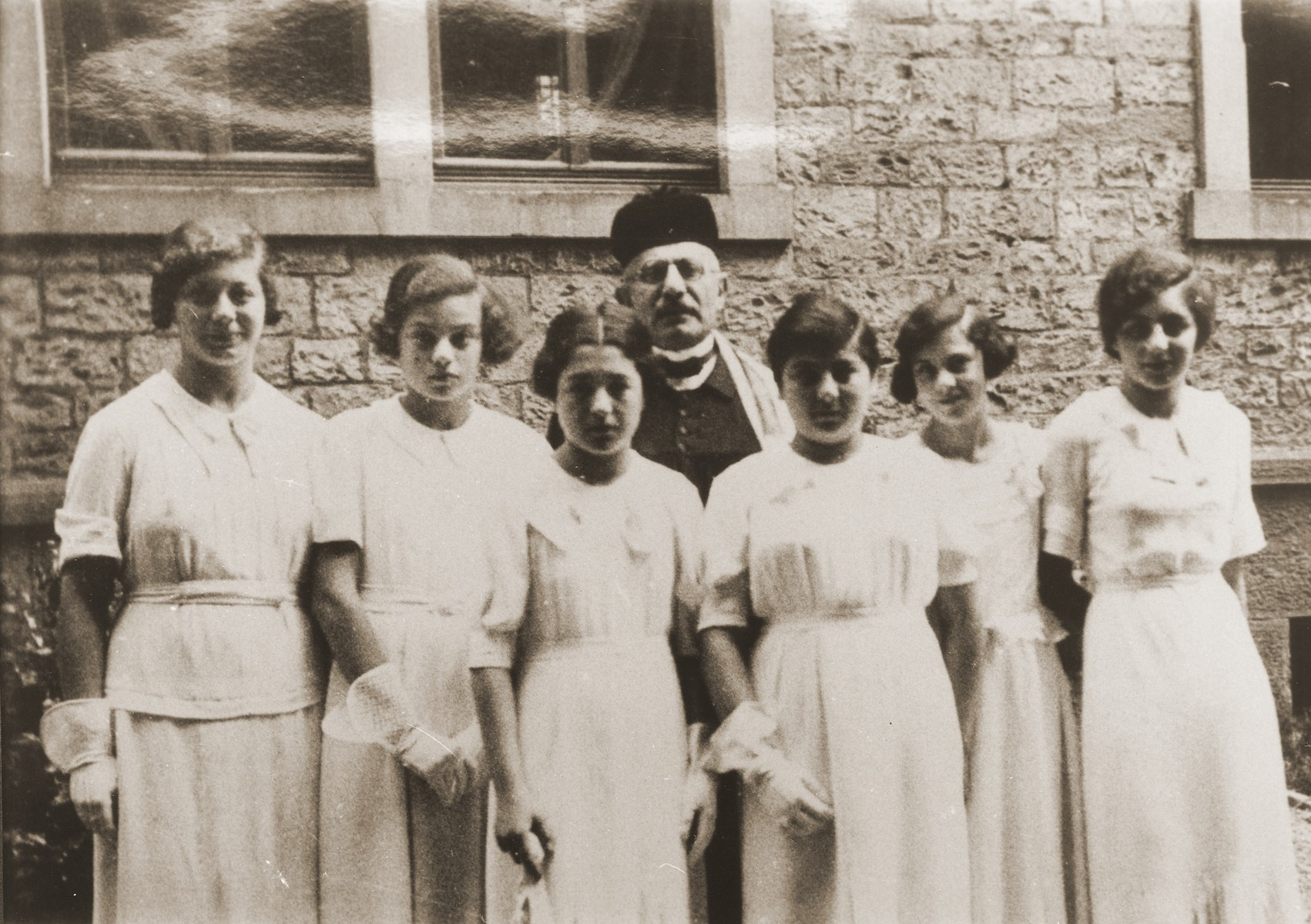 Group portrait of a girls' confirmation class in the courtyard of the liberal Zerrennerstrasse synagogue in Pforzheim.    Pictured from left to right are: Susanne Wolf, Herta Levy, Lore Kahn, Edith Kahn, Ruth Lieben, and Ellen Roos. Cantor David Sommer stands behind them.  All the girls emigrated to the United States by 1940.  Cantor Sommer emigrated to India in 1939.