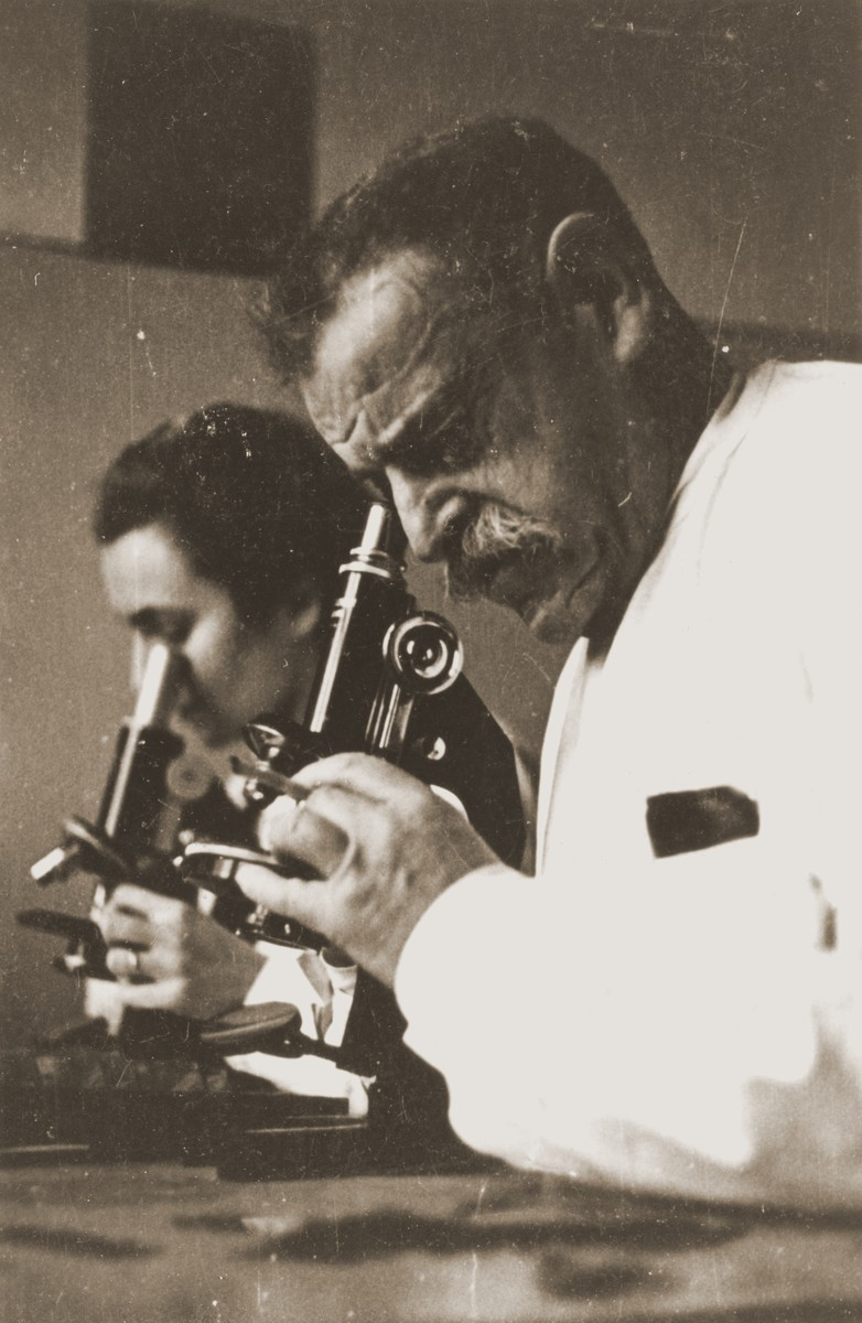 Professor Wilhelm Caspari and a female assistant conduct medical research using microscopes in the laboratory of the main hospital in the Lodz ghetto.  Wilhelm Caspari (1872-1944), was born in Berlin.  He originally studied clinical medicine and became a general practitioner.  In the course of his practice, he turned to bacteriological studies, published a series of scholarly papers, and habilitated as a docent at the University of Berlin.  Cancer research became his area of specialization.  On the basis of his scientific findings, Caspari was offered a chair at the Speyer clinic in Frankfurt am Main, where he worked until the summer of 1933.  He came to the Lodz ghetto in October 1941 with the Frankfurt transport.  Rumkowski immediately accorded him special status, enabling Caspari to continue his research at the main hospital on Lagiewnicka Street.  He was assigned a residence at the rest home in Marysin.  From February, 1942 until December, 1943, Caspari gave talks about nutritional conditions in the ghetto.  After the main hospital was shut down, Caspari was moved to the Department of Vital Statistics, where he compiled tables relating to the mortality rate, and to the caloric and vitamin content of the ghetto diet.  Caspari's wife was deported in September, 1942.  He remained in the ghetto, but his health soon deteriorated.  He contracted influenza during the epidemic of 1943 and succumbed to pneumonia on January 21, 1944.  [L. Dobroszycki, The Chronicle of the Lodz Ghetto 1941-1944, pp.435-6]