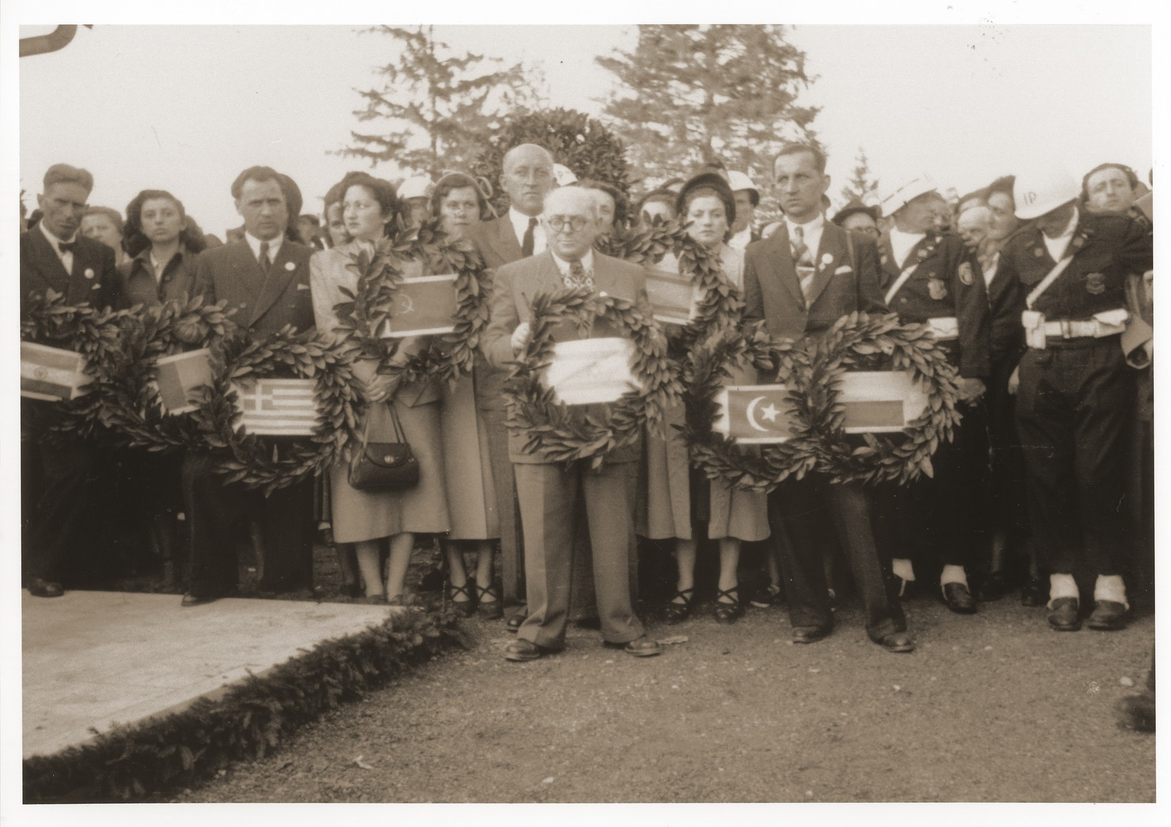 Foreign dignitaries bearing wreaths participate in a memorial ceremony at the Dachau concentration camp.