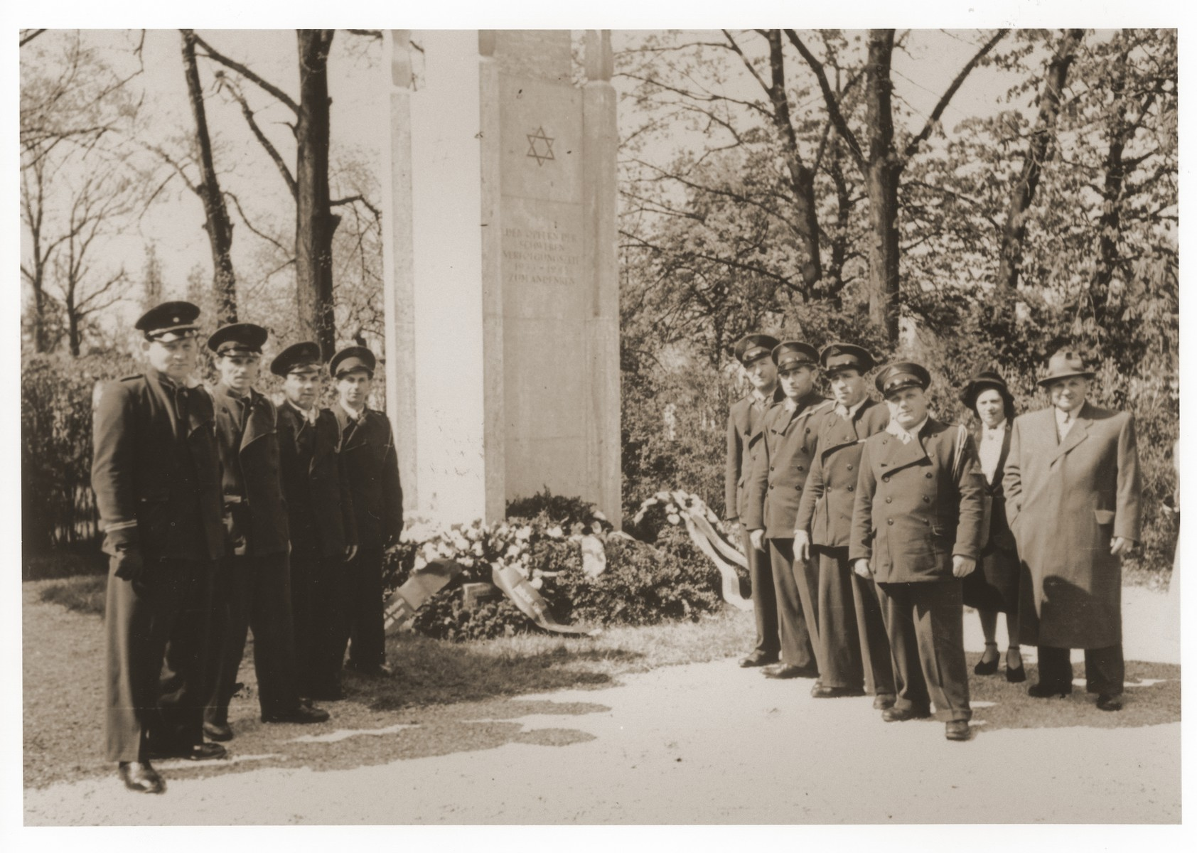 Jewish DP police from the Lechfeld displaced persons camp pose in front of the memorial to Jewish victims at the Dachau concentration camp.