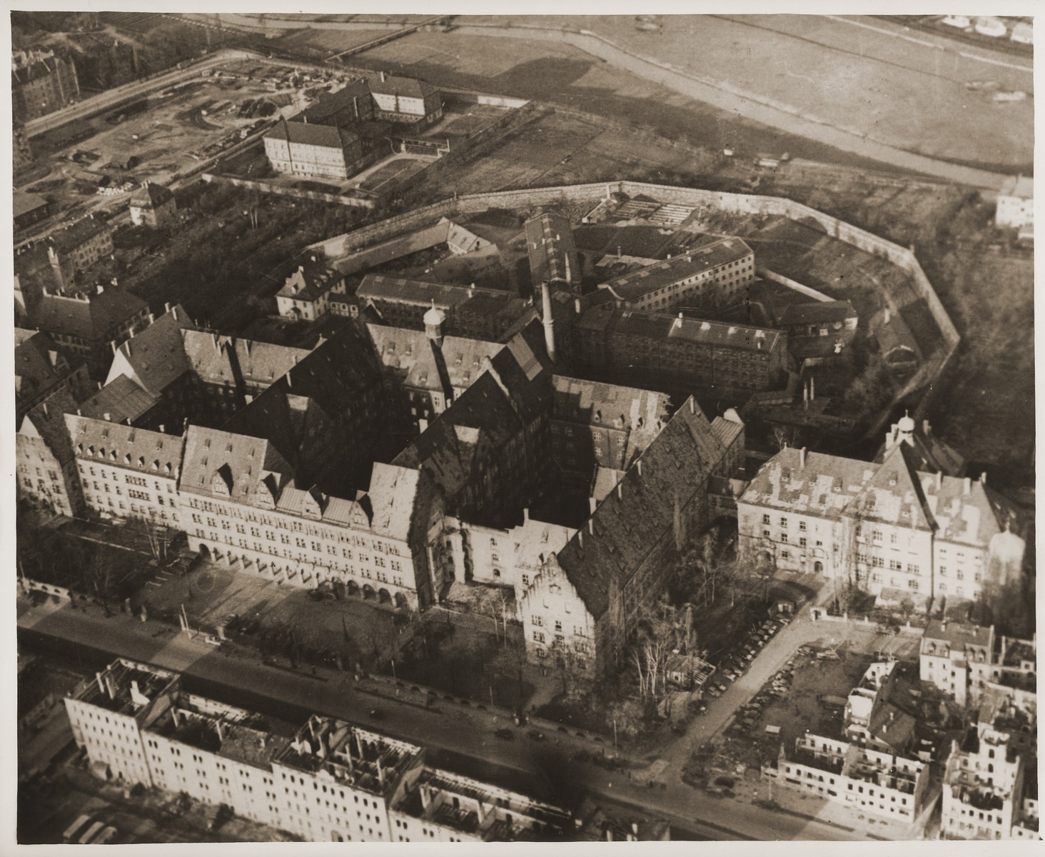 Aerial view of the Nuremberg Palace of Justice and prison, where the war crimes trial of the International Military Tribunal was held and its defendants incarcerated.    In the foreground is the Palace of Justice.  The structure on the right that is connected to the the main building by a passageway, is where the actual courtroom is located.  The main part of the Palace of Justice houses the offices of those working on the IMT.  In the background are the four wings of the Nuremberg prison.  The IMT defendants are housed in the far right wing; the witnesses in the left wing; and other prisoners in the two center wings.