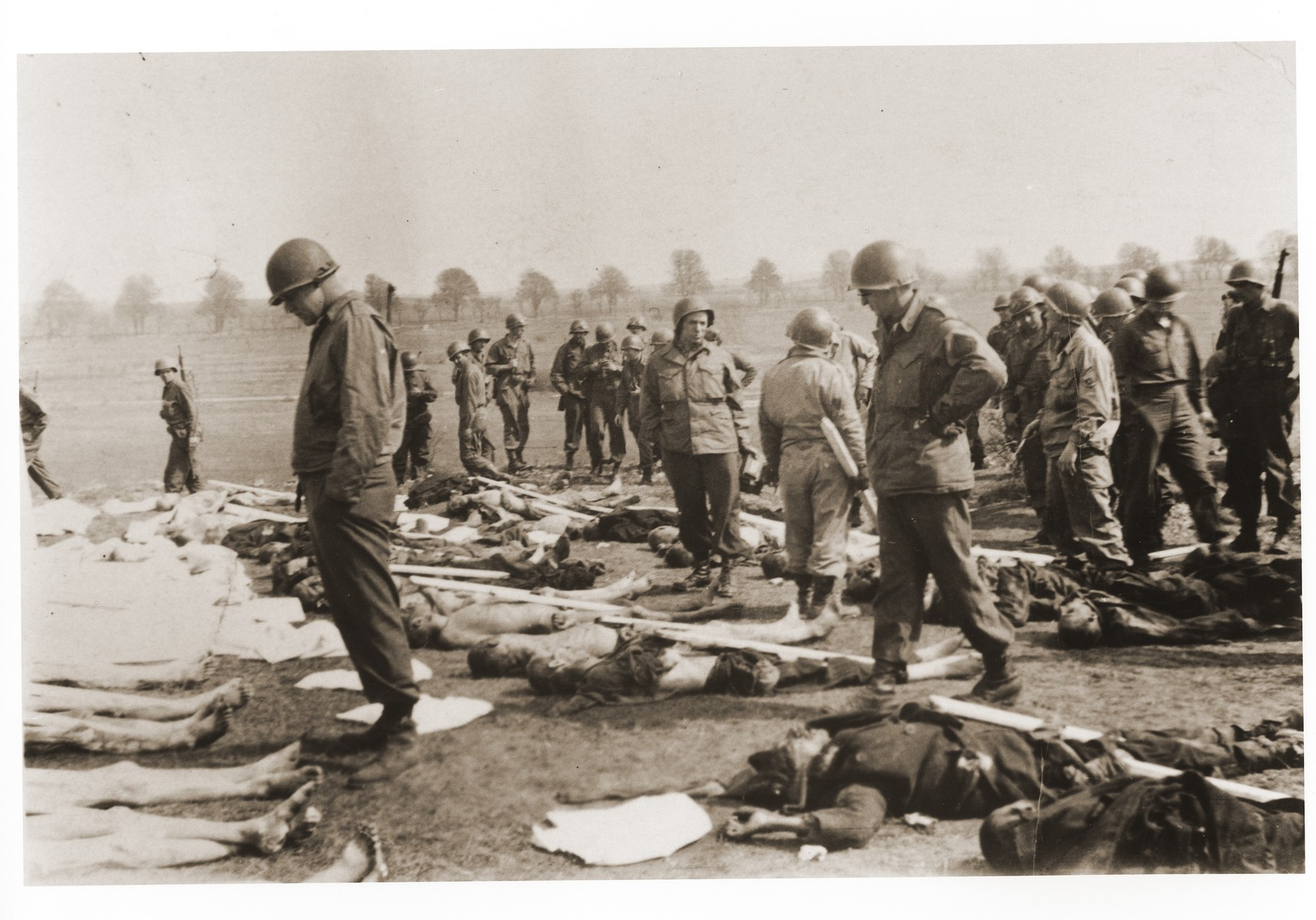 American soldiers view the bodies of prisoners laid out in rows in an open field in the Ohrdruf concentration camp.