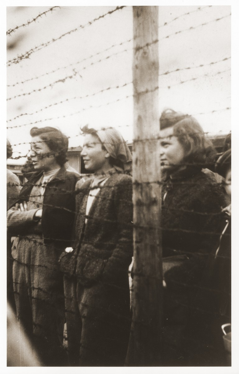 Young female survivors look out from behind the barbed wire fence enclosing the women's camp at Mauthausen.  These women were recent arrivals to Mauthausen, having walked all the way from Vienna.  Many were former teachers from Poland, Hungary, and Czechoslovakia.