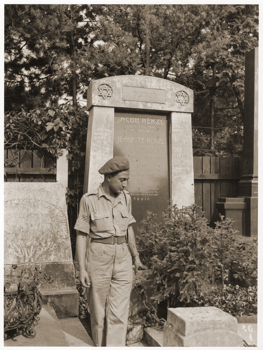 Amos Elhanan, a member of the Jewish Brigade, poses in front of the tomb of Theodor Herzl in Vienna.