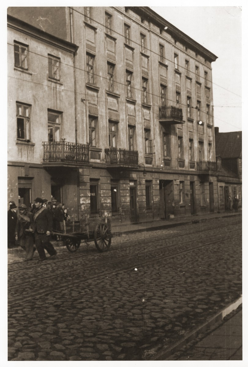 Street scene in the Lodz ghetto with two men pulling a cart.