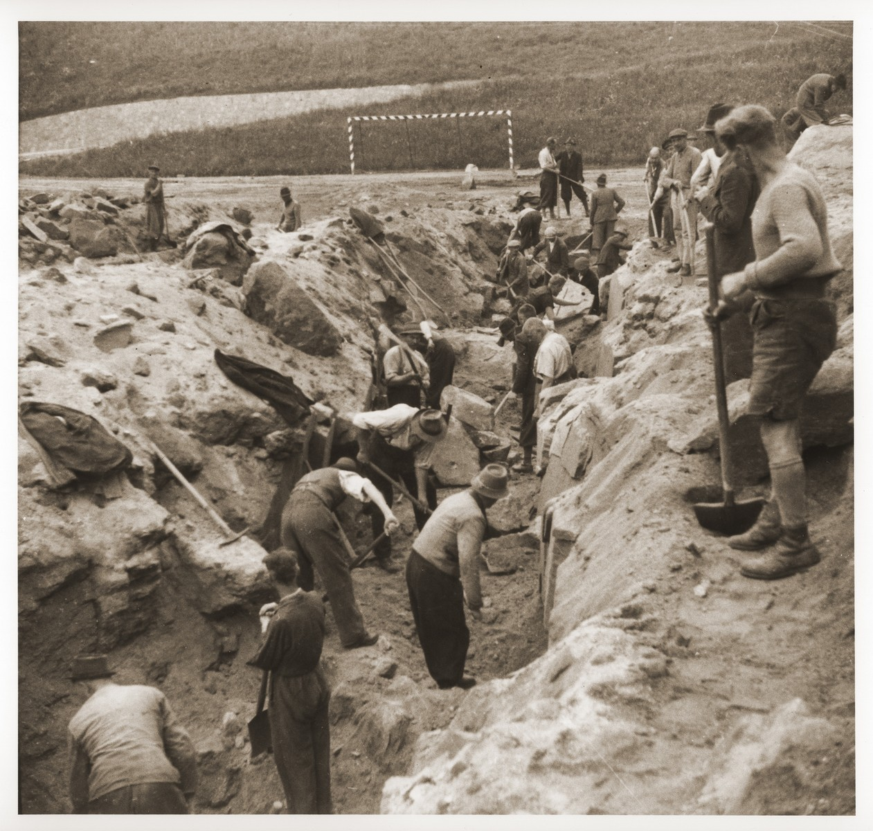 Austrian civilians dig a mass grave in the former SS soccer field in the Mauthausen concentration camp to bury the bodies of former inmates.