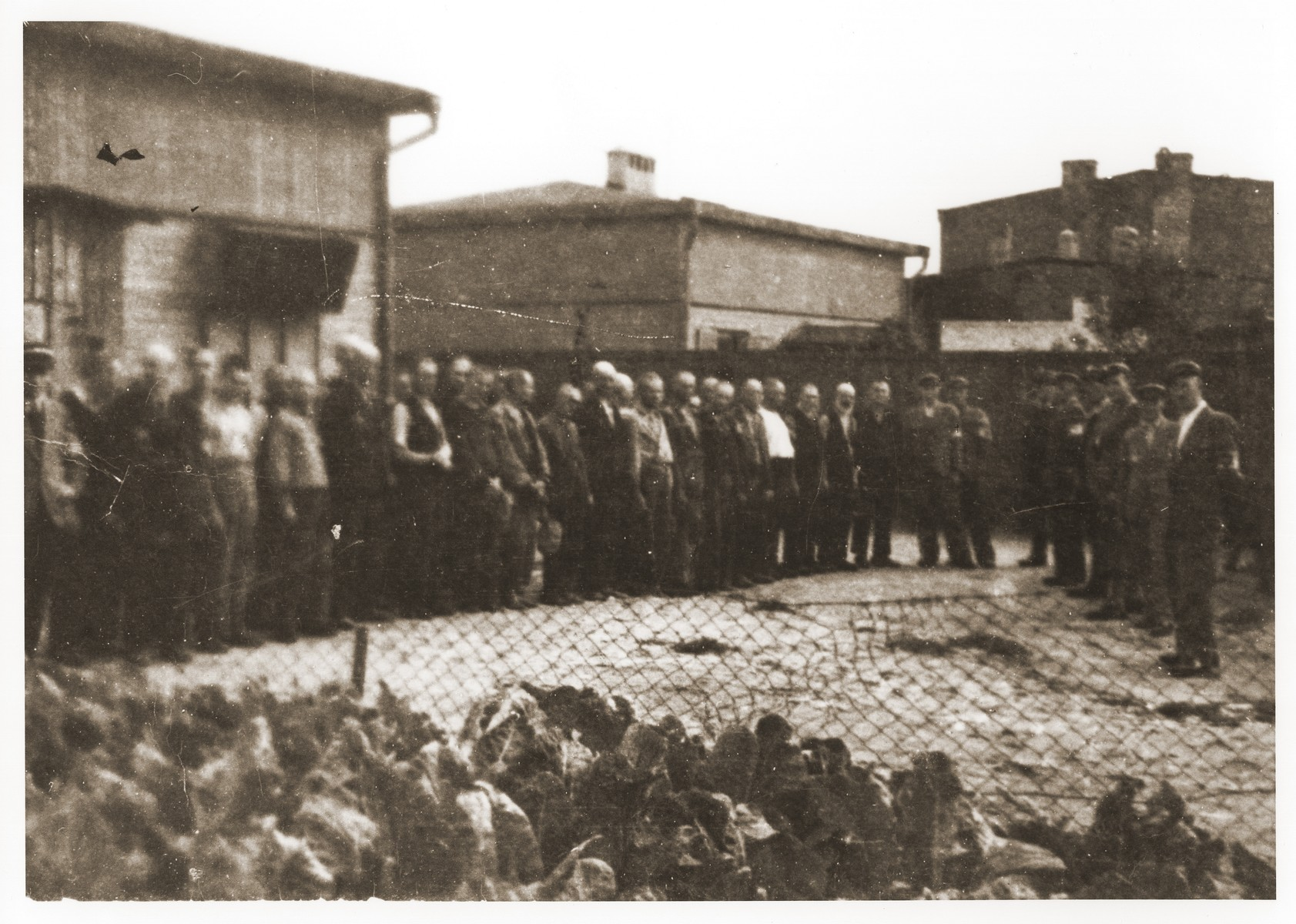 Ghetto police guard a group of Jewish men who have been lined up in the yard of the central prison of the Lodz ghetto.