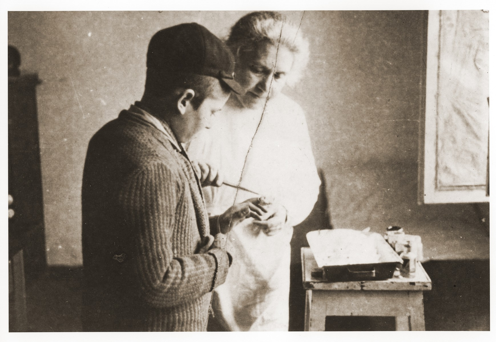 A female physician treats the hand of a youth in the Lodz ghetto.