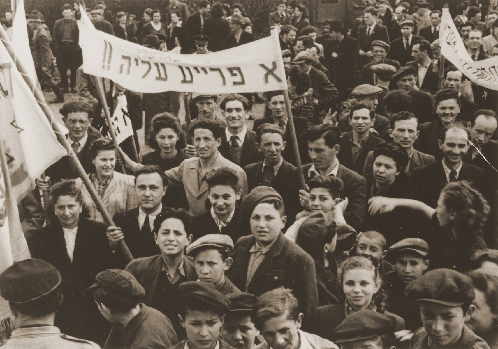 """Jewish DPs in the Feldafing displaced persons camp participate in a demonstration calling for a policy of free immigration to Palestine.  The Yiddish banner reads, """"We support free aliyah [immigration]."""""""