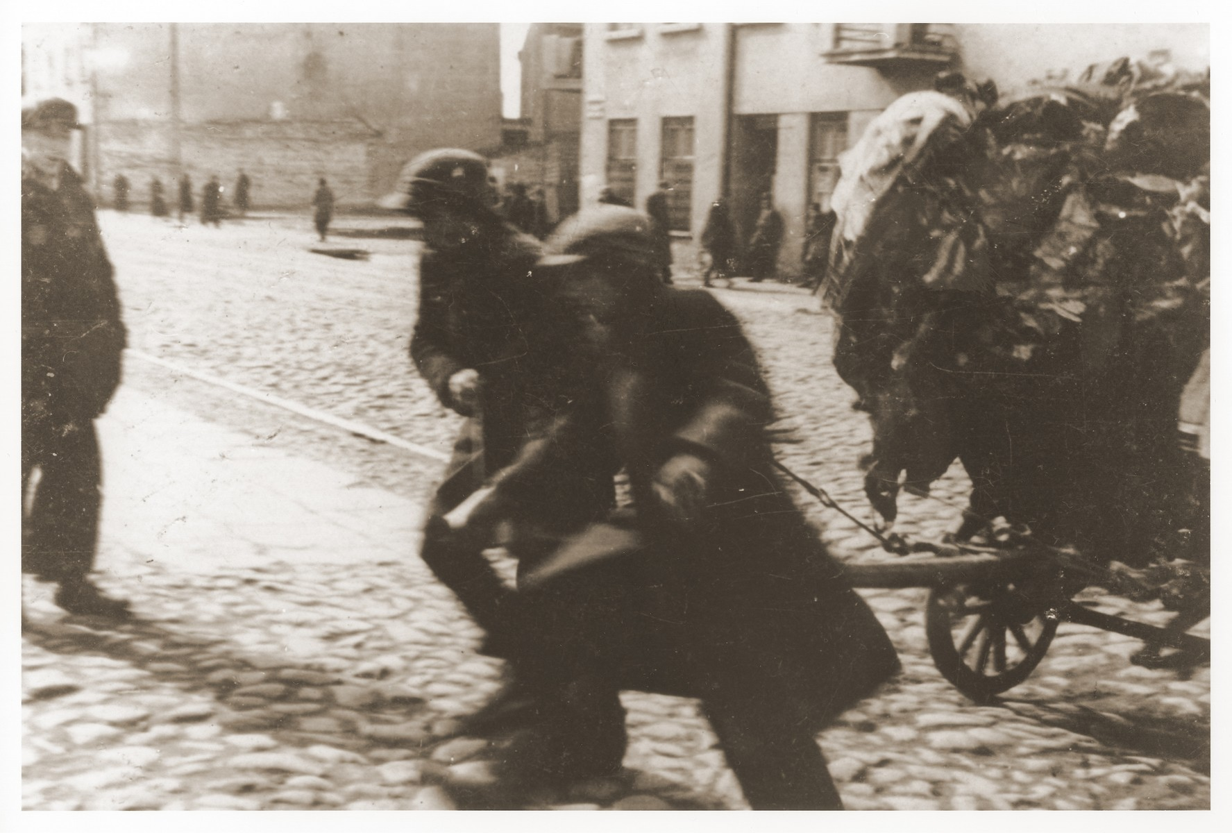 Two men haul a full cart along a cobblestone street in the Lodz ghetto.