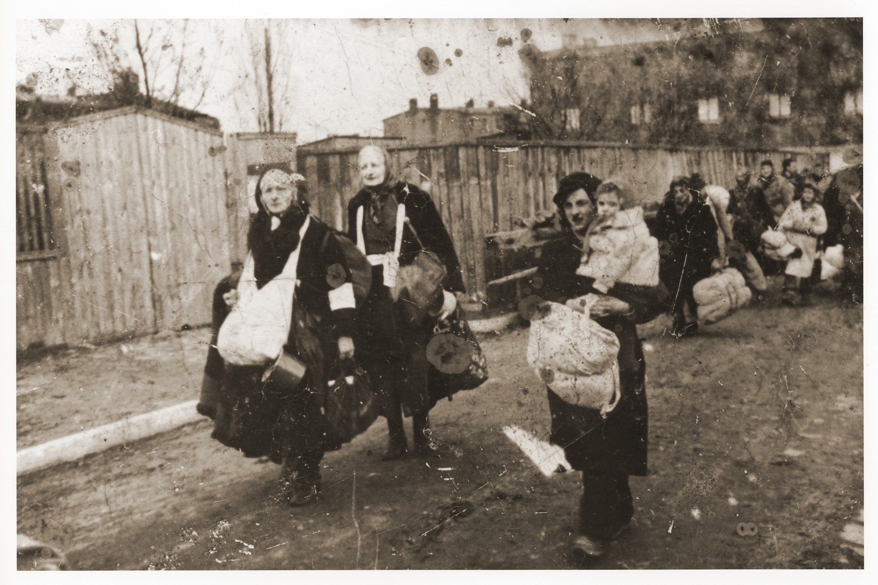 Elderly women carrying young children and bundles of personal belongings trudge along a street in the Lodz ghetto toward the assembly point for deportations to Chelmno.
