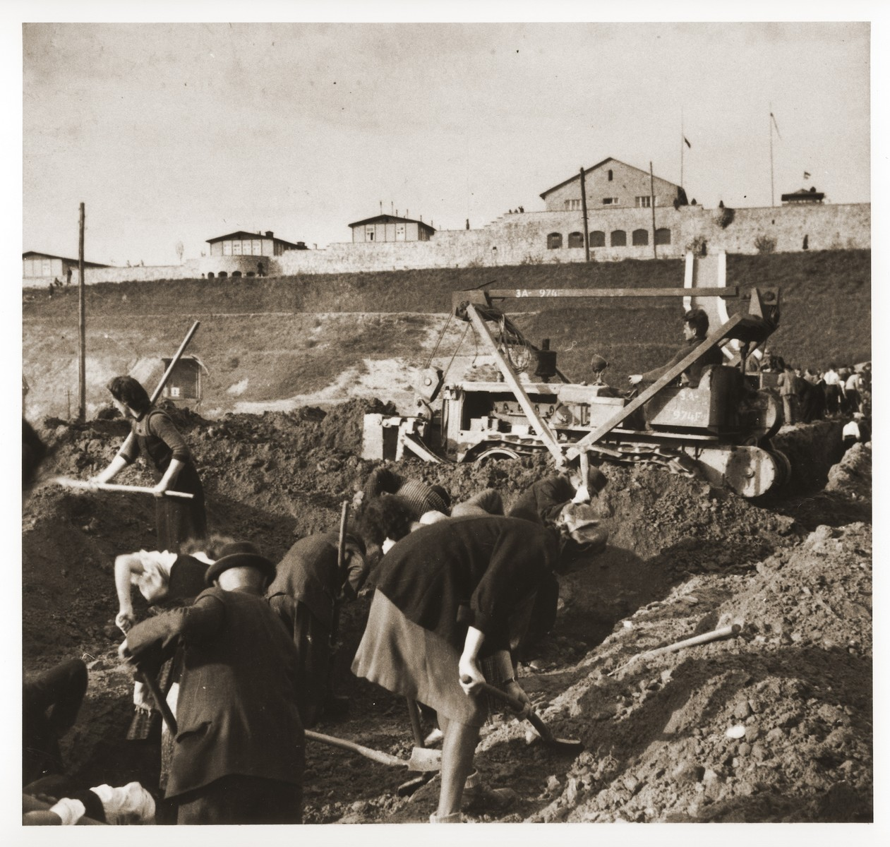 Austrian civilians dig a mass grave in the former SS soccer field in the Mauthausen concentration camp to bury the bodies of former inmates.    An American soldier, Elmer Salsman of the 56th Engineering Corps, drives a bulldozer in the background.