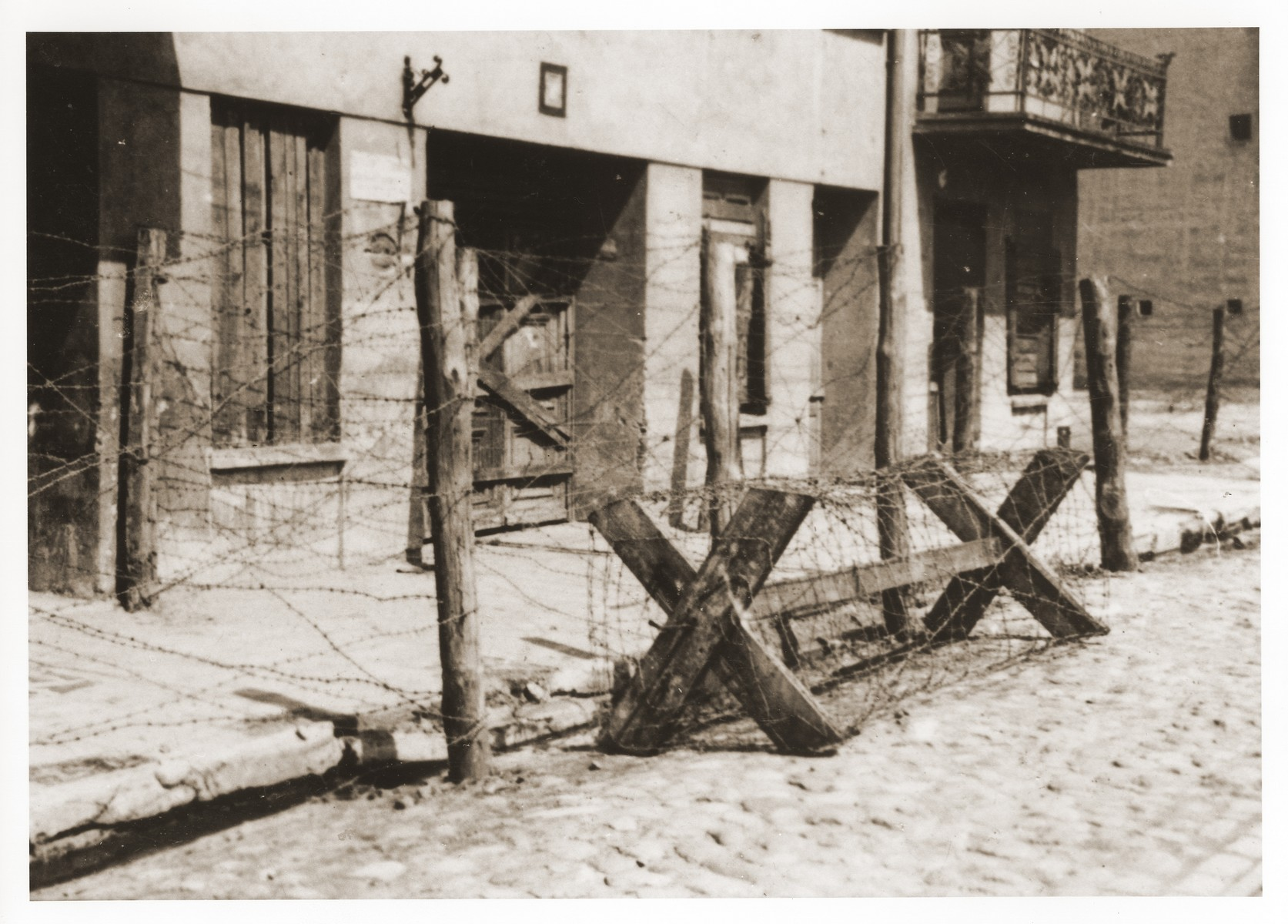 View of the entrance to the Gypsy camp on Brzezinska Street in the Lodz ghetto after its liquidation.  In the fall of 1941, 5007 Austrian Gypsies of the Lalleri tribe were deported to Lodz, where they were housed in a block of buildings on Brzezinska Street.  The Gypsy camp was adjacent to the ghetto but separated from it by a barbed-wire enclosure.  The Gypsy population remained only for a few months before being deported with the first transports to Chelmno early in 1942.