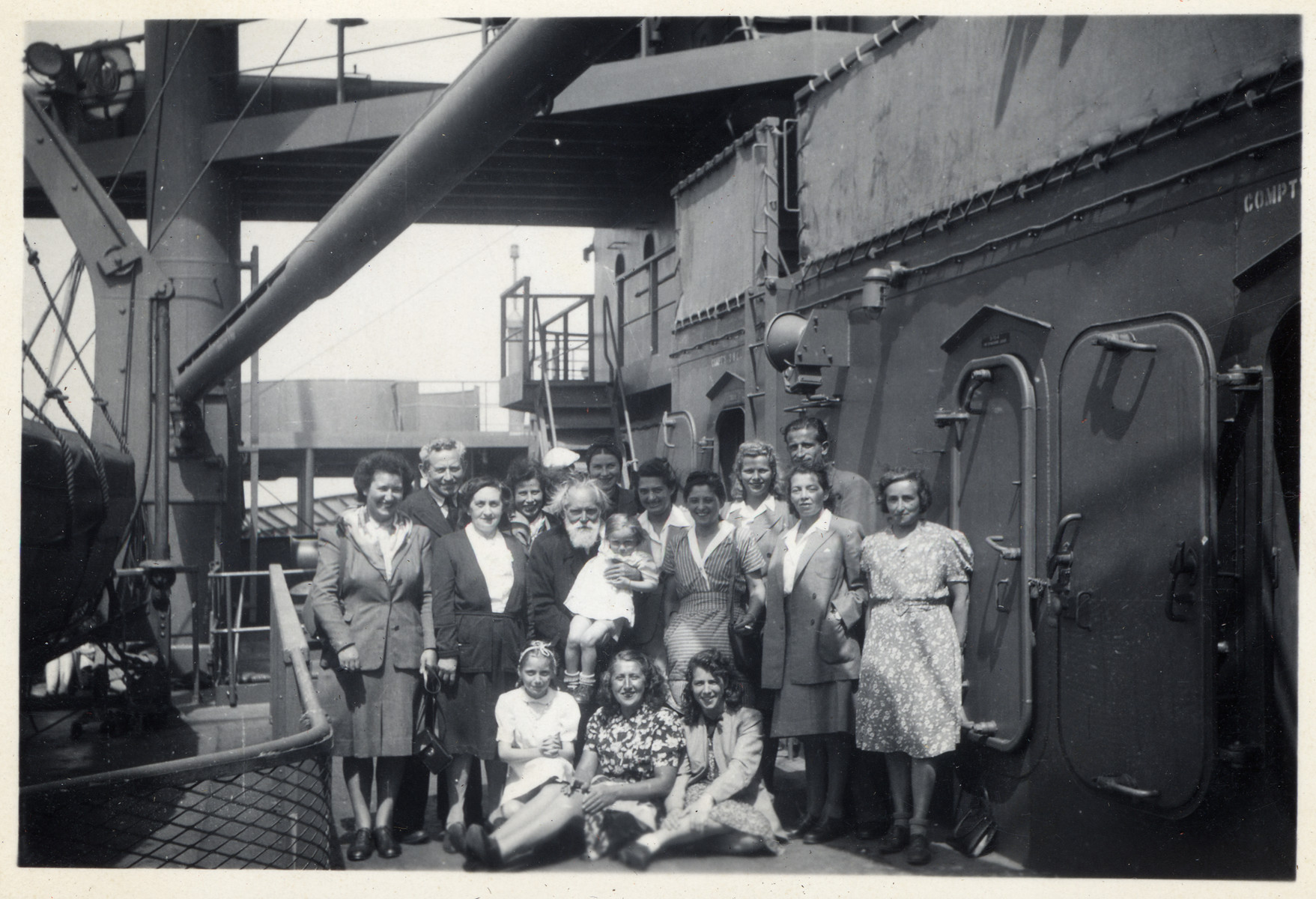 Group portrait of passengers aboard the Marine Perch who are immigrating to the United States after the war.  Among those pictured are Marion (standing on the far left) and Jachet Sauerbrunn (sitting in the center).