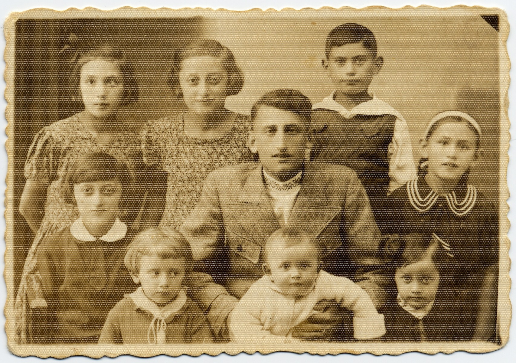 """Group portrait of Meir Holcman, donor's father, with his eight nieces and nephews.    The portrait was taken shortly before Meir left for Palestine.  All the children perished in Chelmno in 1942.  Pictured, standing in the back row, from left are: Hela Bauman, daughter of Golda Itta; Andzia (Chana) Holcman, daughter of Josef; Eli Holcman, son of """"Bucik."""" In the front row, from left are: Szajna Holcman, daughter of Josef; Chana Holcman, daughter of Moshe Aron; Eli Holcman, son of Abram Icchak and Chana Holcman, daughter of Hersz Lejzor."""