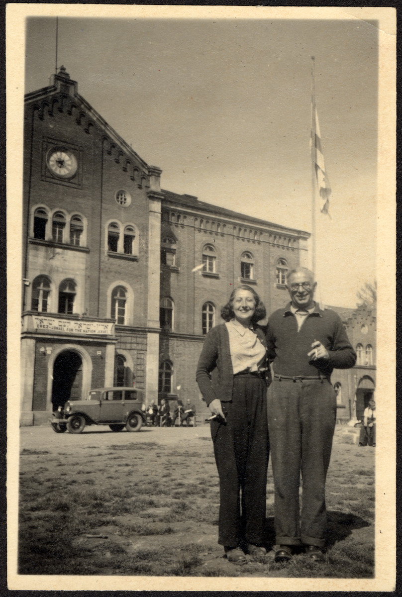 "A husband and wife who survived Theresienstadt pose outside the main building of the Deggendorf displaced persons' camp.  The sign on the building reads ""The Land of Israel for the Nation of Israel"".  Pictured are Jachet and Fritz Sauerbrunn."