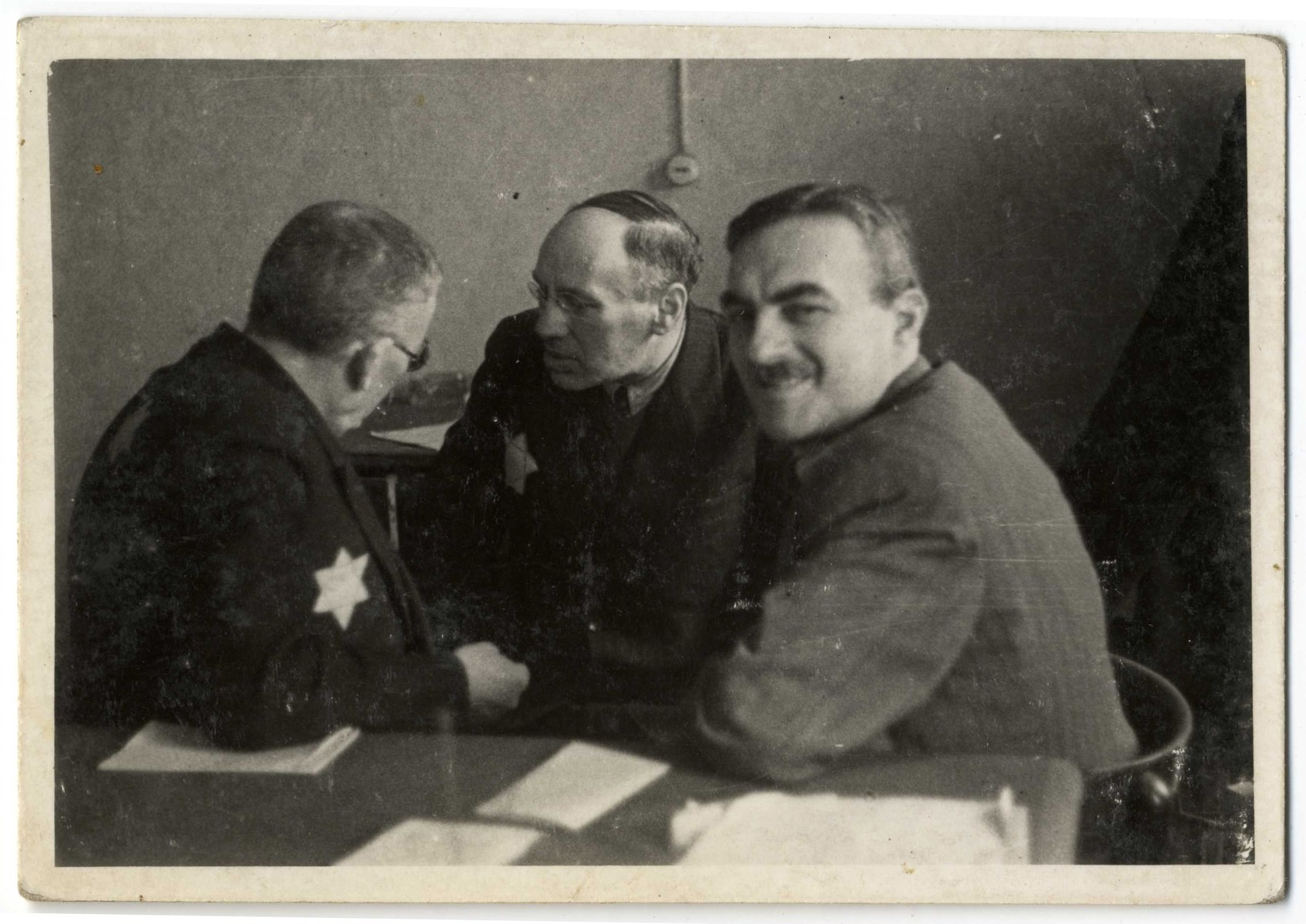 Directors of Lodz ghetto workshops meet in an office.   Pictured on the far right is Gustaw Gerson, the director of the Zentral Einkaufstelle.  In the center is Dawid Warszawski, head of the textile workshops.