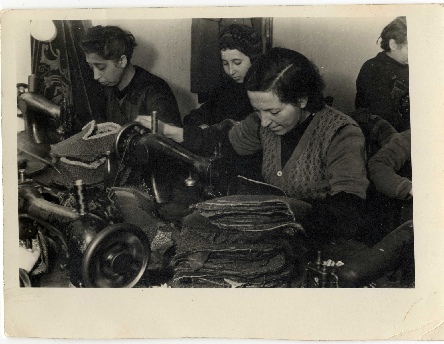 Women sew cloth slippers in one of the workshops in the Lodz ghetto.