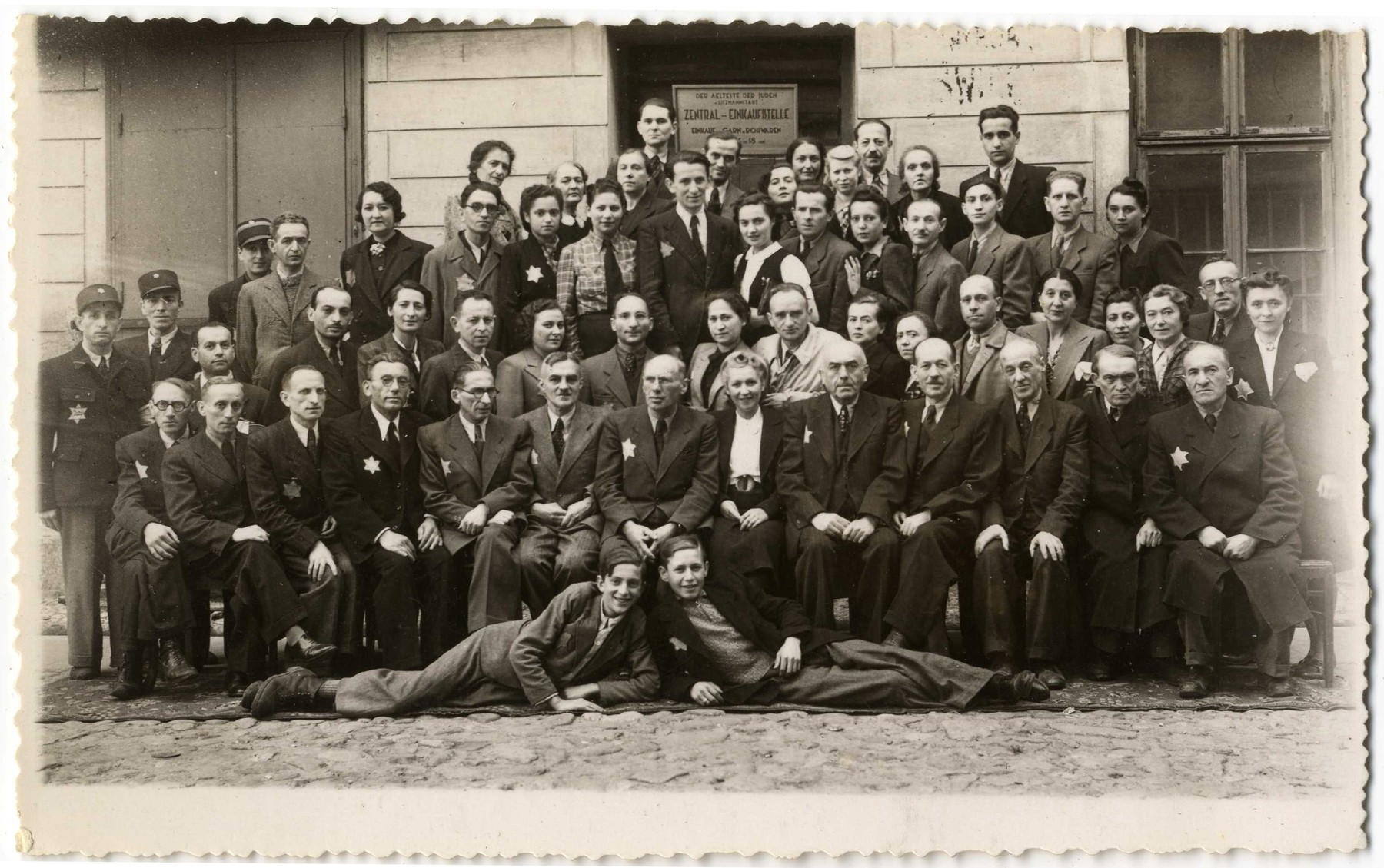 Group portrait of the employees of the Zentral Einkaufstelle, the central purchasing department of the ghetto which provided raw materials to the other ghetto workshops.  Pictured in the front row, sixth from the left is Gustaw Gerson, the director of the Einkaufstelle.  To his immediate right and in the center of the photograph is Dawid Warszawski, head of the textile workshops.