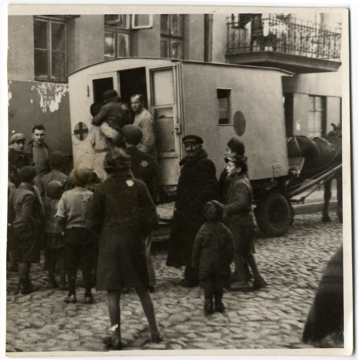 A young child is carried into a horse-drawn ambulance while other children gather around to watch.