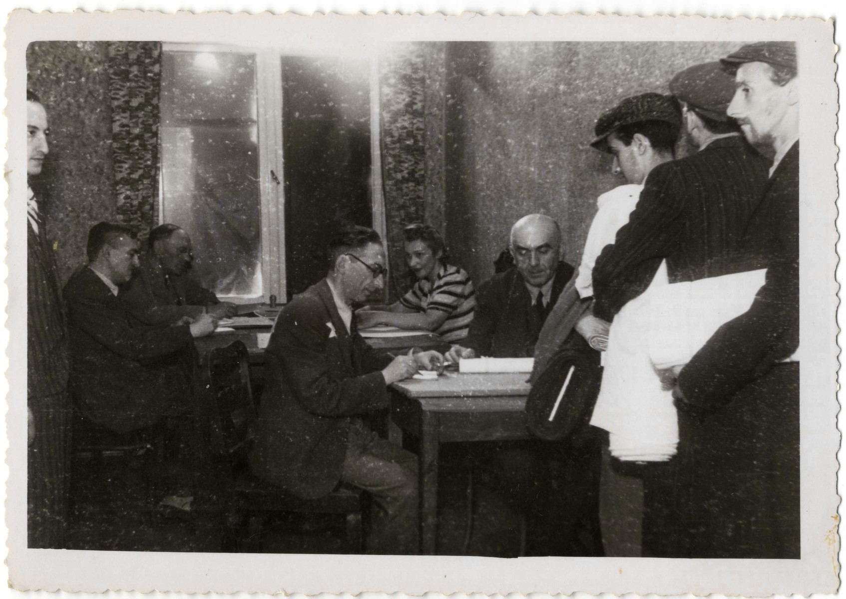 Employees of  the Zentral Einkaufstelle, the central purchasing department of the ghetto, process the distribution of bolts of cloth.  Seated in the back left is Gustaw Gerson, the director of the Einkaufstelle.  Seated directly behind him is Dawid Warszawski, head of the textile workshops.