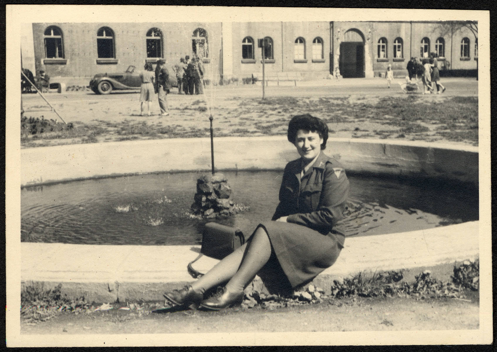 Close-up portrait of a young female censor for the American army sitting on the edge of a fountain in the Deggendorf displaced person.  Pictured is Marion Sauerbrunn.