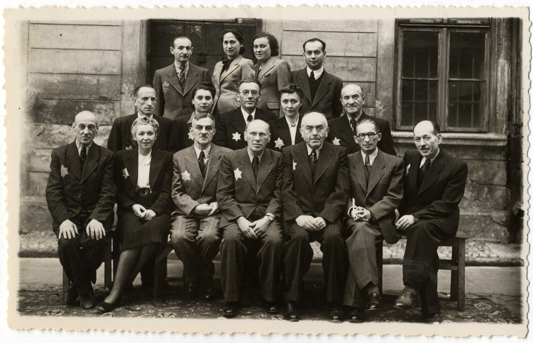 Group portrait of the employees of the Zentral Einkaufstelle, the central supply warehouse of the ghetto which provided raw materials to the other ghetto workshops.  Pictured in the front row, second from the left is Stefa (the secretary), third from the left is Gustaw Gerson, the director of the Einkaufstelle.  To his immediate right and in the center of the photograph is Dawid Warszawski, head of the textile workshops, and next to him is Lipnowski, co-director of the Einkaufstelle.