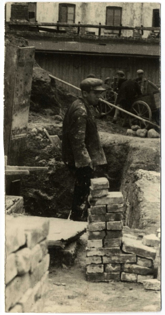 A worker lays bricks in a construction site in the Lodz ghetto.