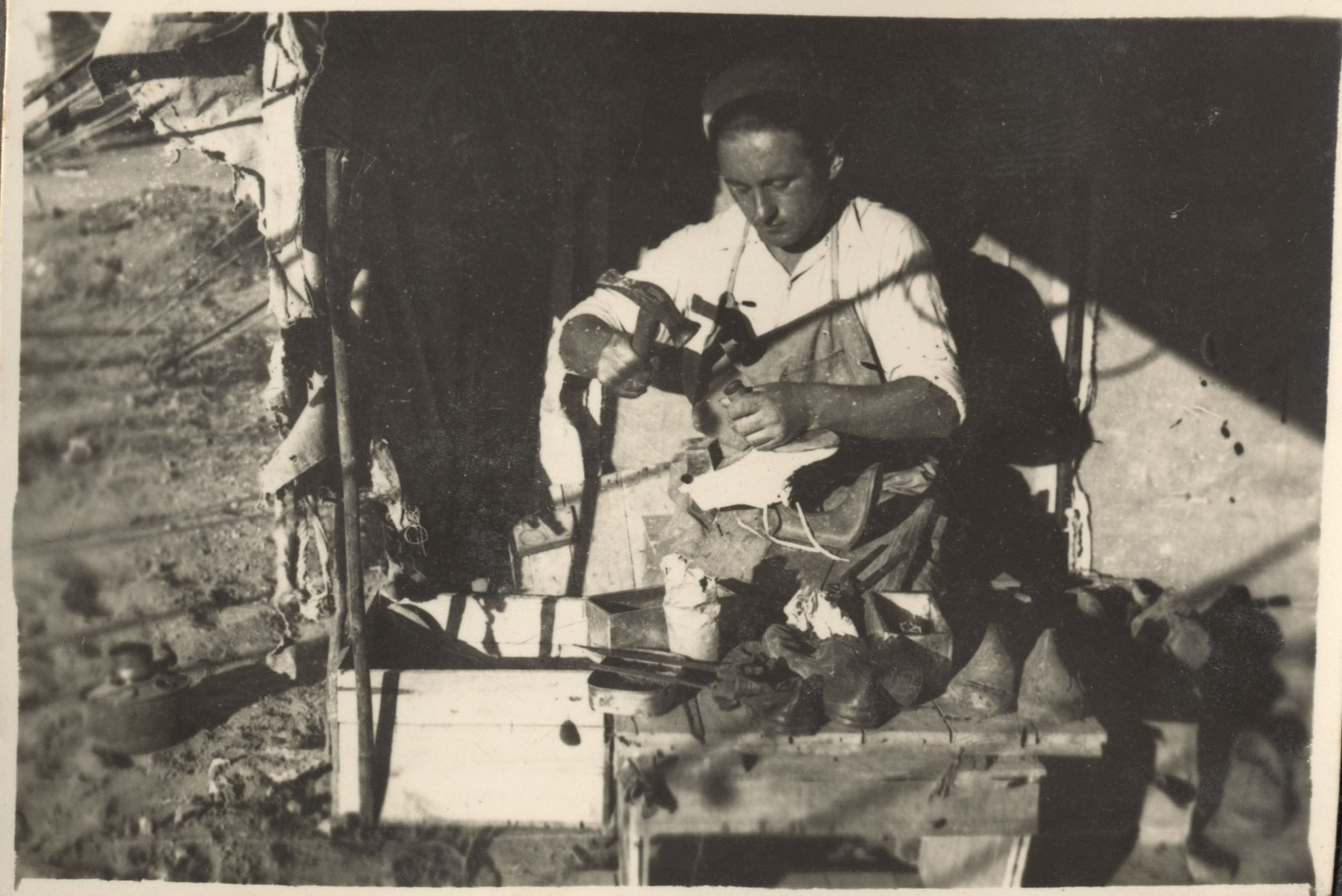 A cobbler works at the entrance to his shop in one of the camps on Cyprus.
