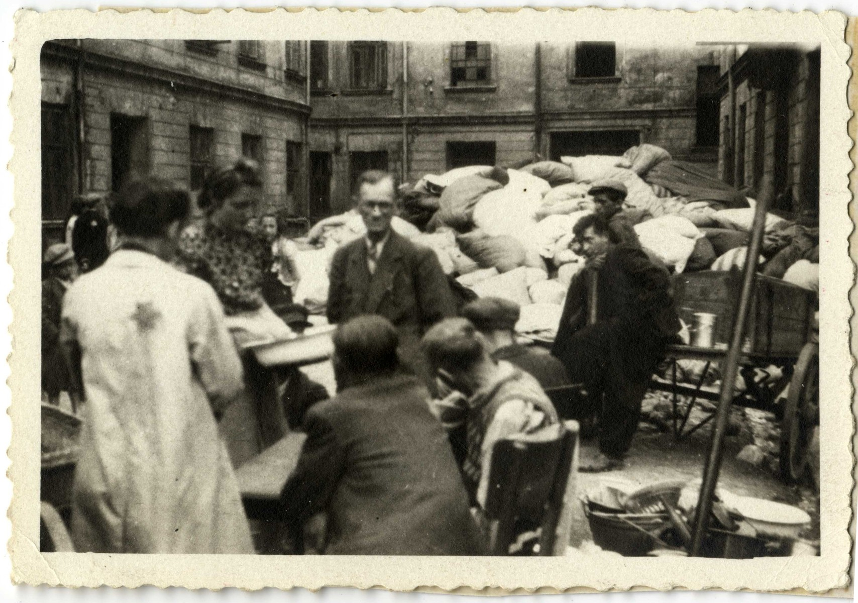 Workers in the Lodz ghetto organize a pile of abandoned personal belongings, perhaps after a deportation.