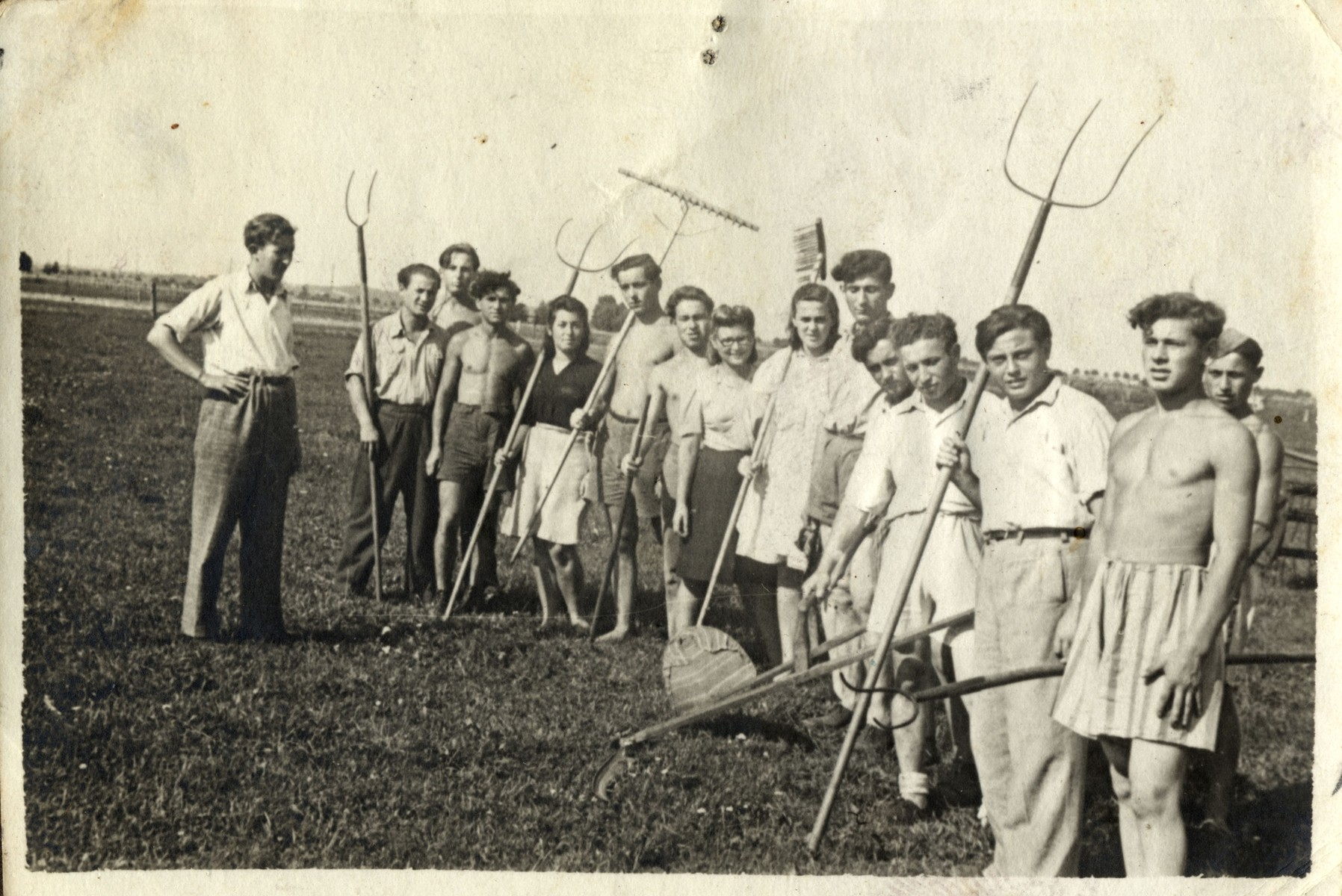 Group portrait of Jewish youth holding farming tools in a kibbutz hachshara in Germany.    Standing on the far left is probably the donor, Henryk Bergman.