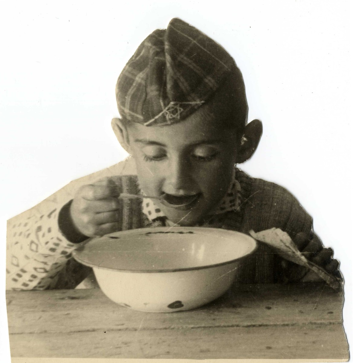 Close-up portrait of a young boy eating soup in the Lodz ghetto.