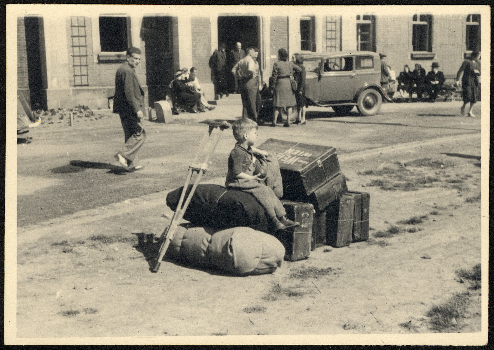A young child sits among suitcases and a crutch while waiting to depart the Deggendorf displaced persons' camp.