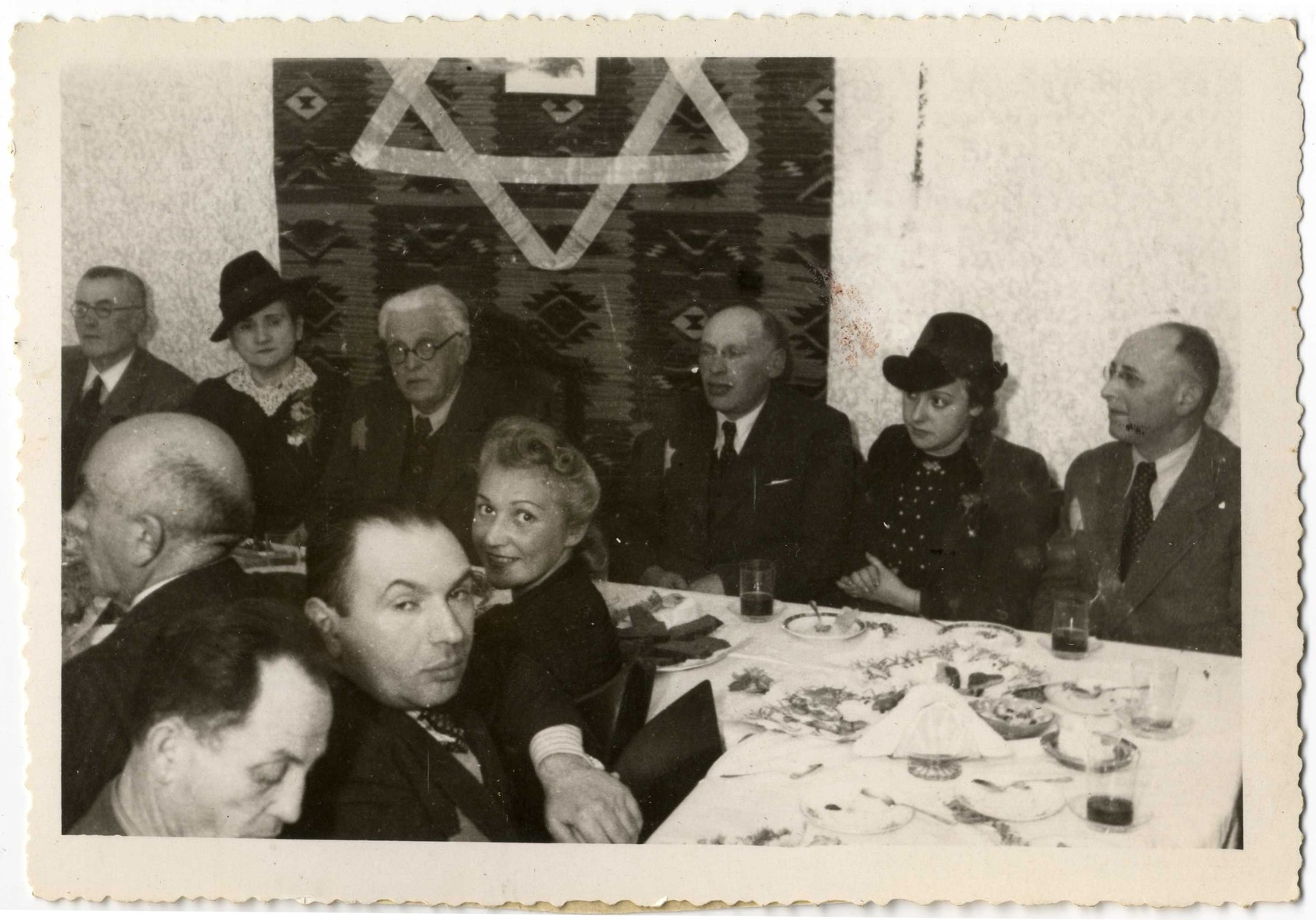 Ghetto officials gather for a festive meal in front of a wall hanging with a large Jewish star.  Seated in the center of the table is Chairman, Mordechai Chaim Rumkowski.  To his left is his sister-in-law Helena Rumkowski.  To his right are Dawid Warszawski and Dora Fuks.