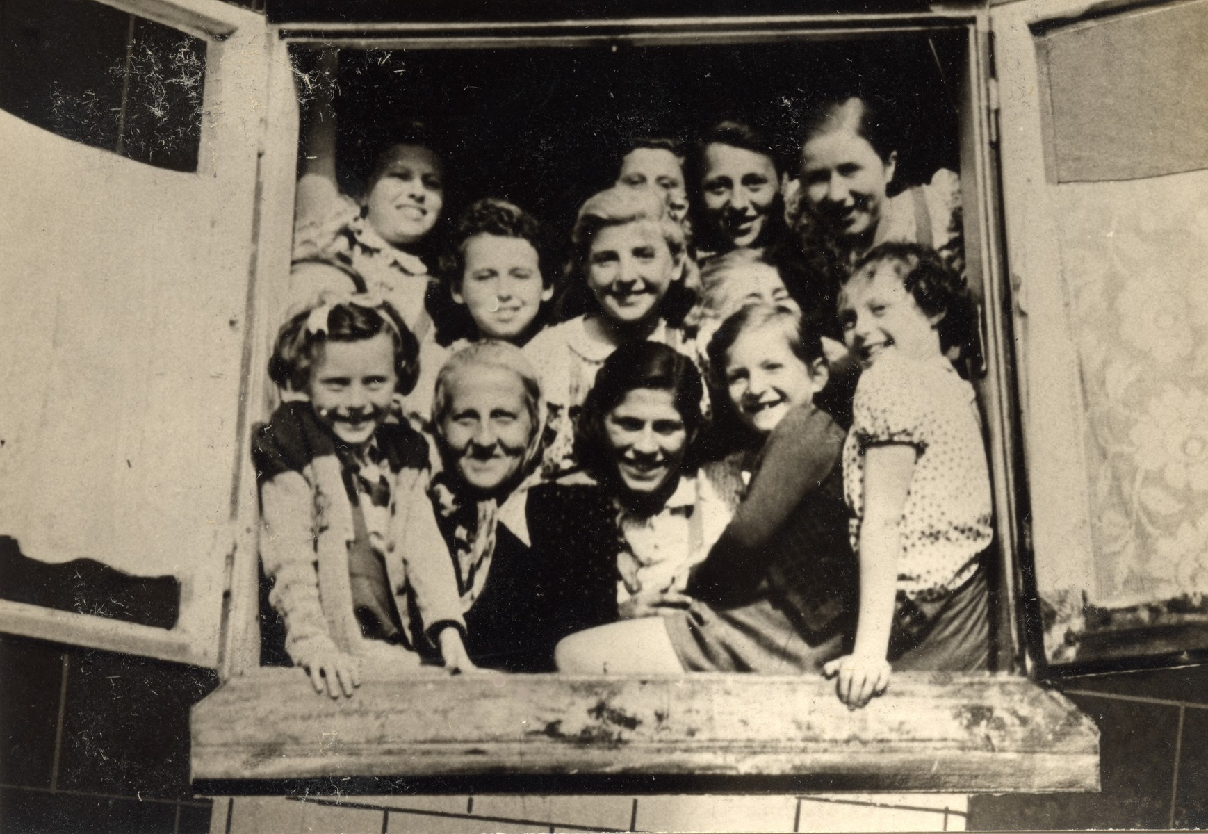Stella Rein, the headmaster of the Lodz ghetto's high-school, posing with young girls.   Pictured in the front row, right, is Felicia (Faiga) Ferszter, daughter of Leon (Leib) Ferszter and his first wife Zelda (nee Asz) Ferszter.  Felicia was born in February 1931 in Lodz and died with her mother in Auschwitz in August 1944.