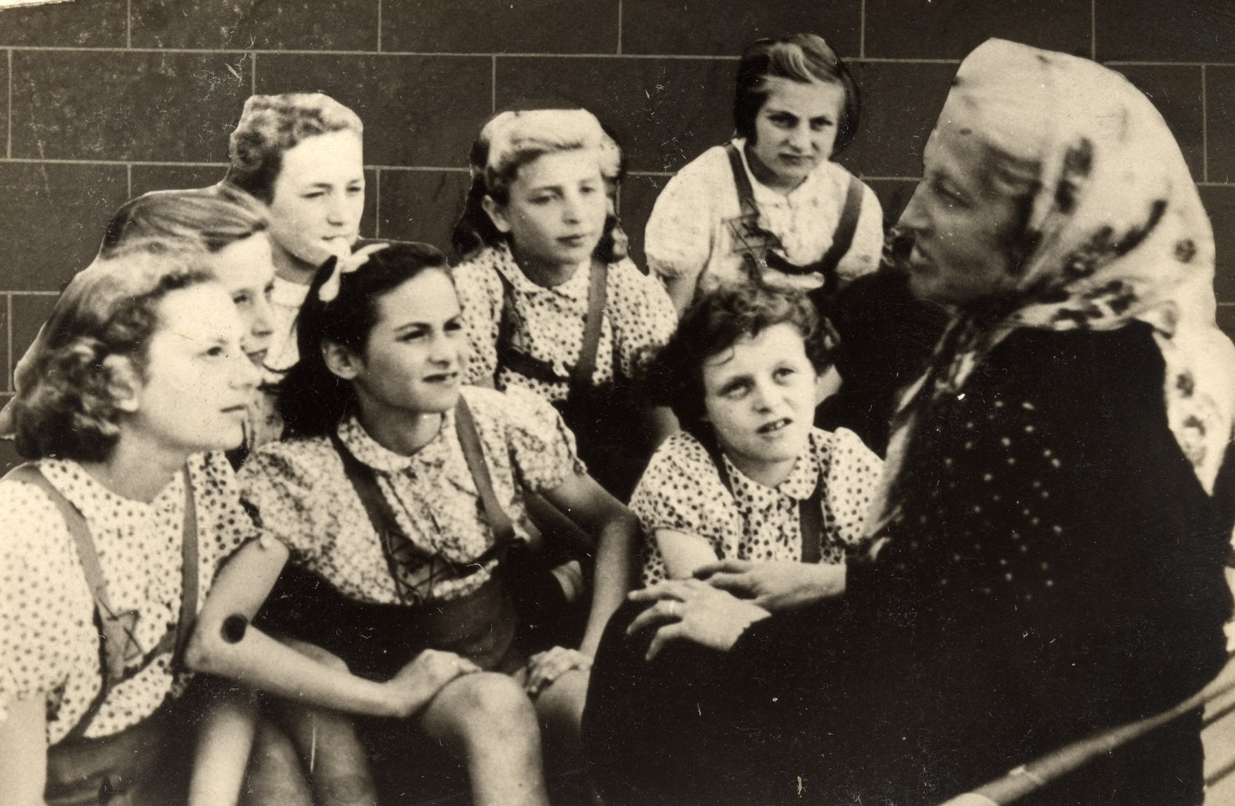 Stella Rein, the headmaster of the Lodz ghetto's high-school, talks to a group of young girls wearing similar blouses.   Pictured in the front row, right, is Felicia (Faiga) Ferszter, daughter of Leon (Leib) Ferszter and his first wife Zelda (nee Asz) Ferszter.  Felicia was born in February 1931 in Lodz and died with her mother in Auschwitz in August 1944.