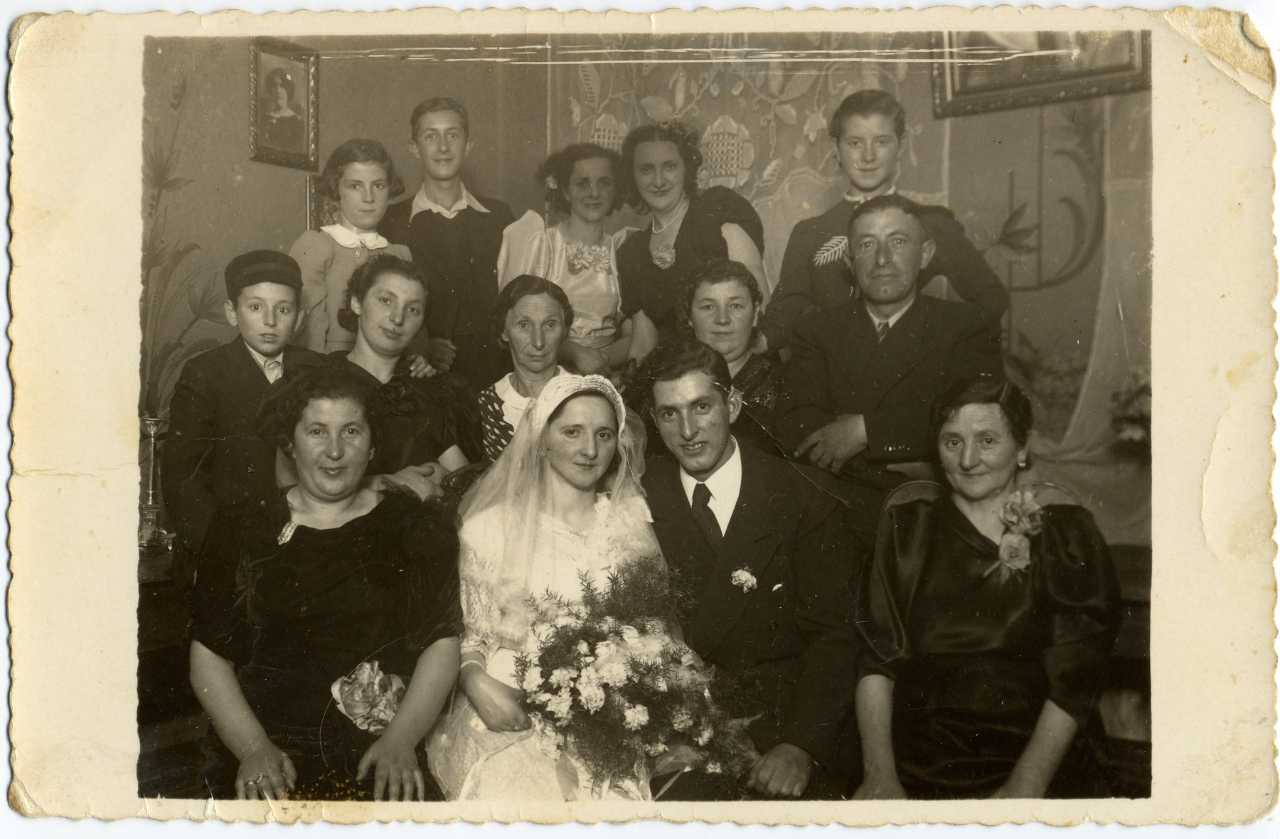 Wedding portrait of Pinkus Bergman and Rutka Most.   Pinkus Bergman, the donor's brother, was mobilized into the Polish army in September 1939 and did not return from the front.  Rutka died in the Lodz ghetto.   Pictured from left to right in the first row from the bottom are: Frymet Bergman, Rutka Most, Pinkus Bergman, and the mother of the bride.  In the second row, from left to right are: Abram Popinski, Frymet Szajnik (Bergfajnd), Estera Fraidel Szajnik, Chana Hinda Popinski, and Benjamin Bergman.  In the top row, from left to right, are: Toba Popinski (now Katzenstein), Henryk Bergman, the donor, the bride's sisters and Rywka Popinski.