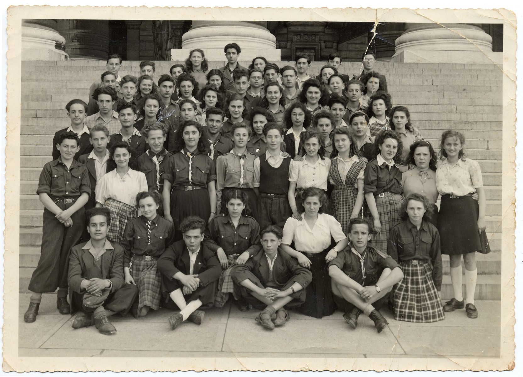 Group portrait of members of the Gordonia Zionist youth movement on the steps of the Palais de Justice in Brussels.   Esther Baczynski, the donor's wife, was the leader of this group and is pictured standing third from right in the third row from the bottom.