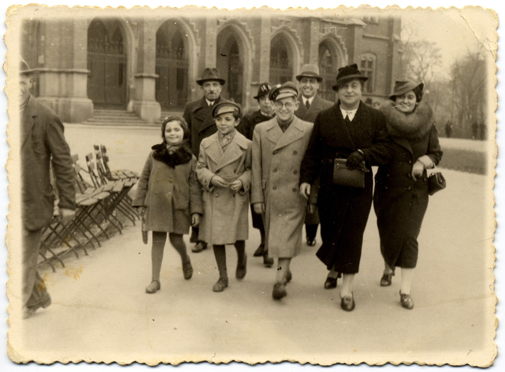 Group portrait of adults and children walking in front of the Jagiellonski University in Krakow.   Pictured in the front row, from left to right are Dola and Josef Horowitz, unknown, Esther? Zehnwirth and Rozia Lesser.  In the back row, from left to right, are: Chaim and Fela Horowitz, and Fela's brother, Monek Lesser who had just graduated from the Medical Faculty of the Jagiellonski University.