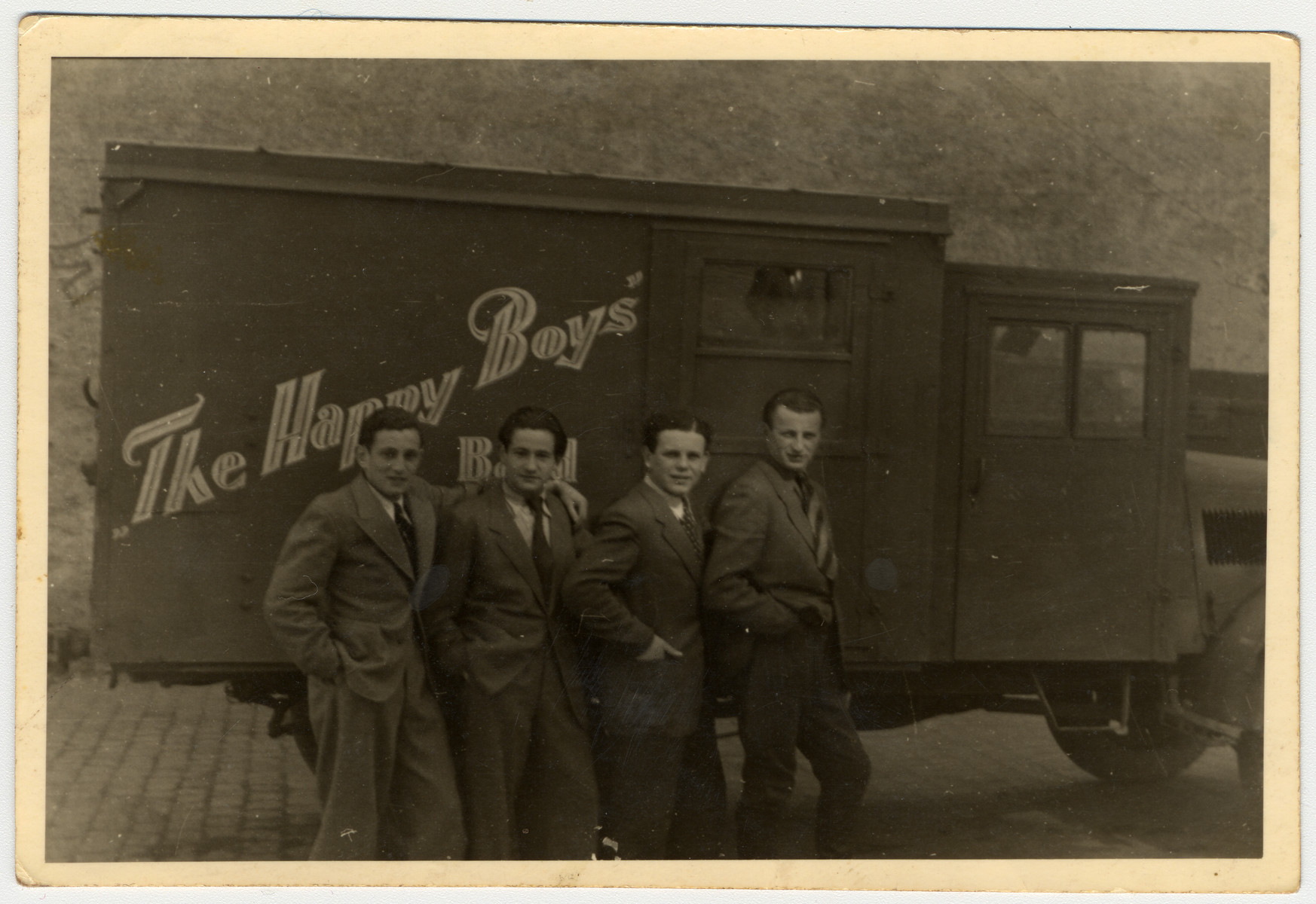 "Four survivors of the Lodz ghetto pose in front of a truck labeled ""The Happy Boys"" in a DP camp in Germany.   First and second from the left are Leon Kniker (now Kent) and Romek Kniker (now Kent), the donor's brothers.   ""The Happy Boys"" was a swing and jazz band which performed at DP camps throughout Germany from 1945-49.  Many of its members had previously been musicians in the Lodz ghetto."
