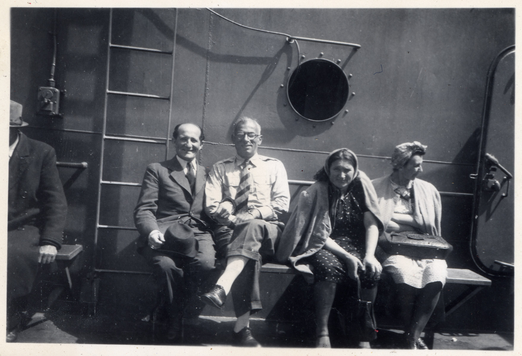 German-Jewish passengers sit on the deck of the Marine Perch en route to the United States after the war.  Among those pictured is Fritz Sauerbrunn, donor's father (second from left).