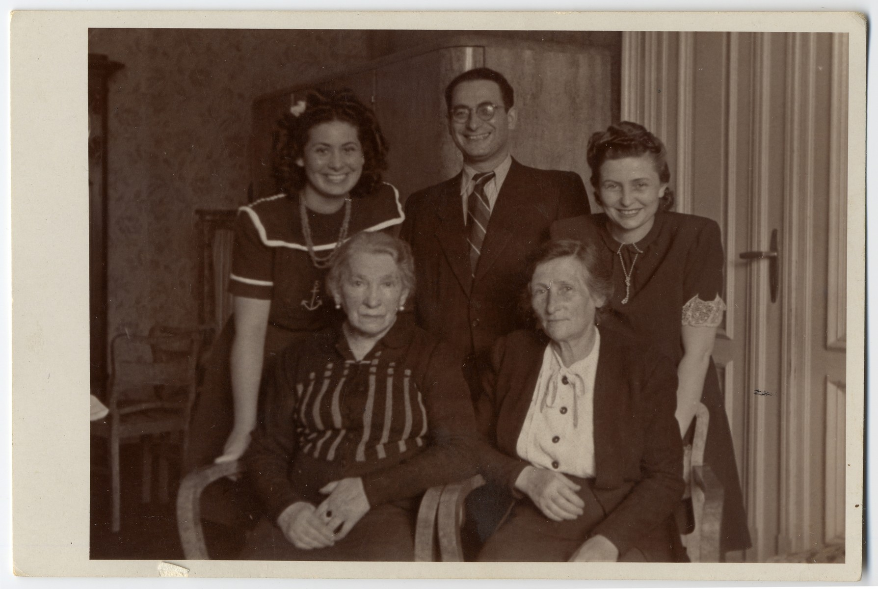 Group portrait of survivors from the Lodz ghetto.  Standing, from left to right, are the donor, Ruth Berlinska, her uncle, Leon Fajtlowicz, who was in charge of all the leather workshops in the Lodz ghetto, and his wife Cesia.  Seated are Leon's mother, Ester Fajtlowicz and Cesia's mother, Towa Golab, both of whom survived in hiding.