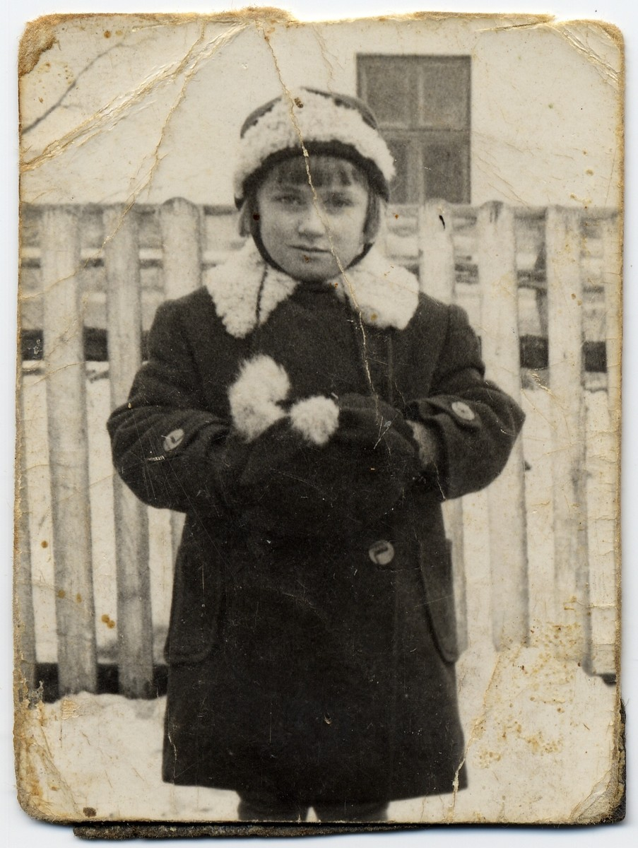 Portrait of a girl in a winter coat standing in front of a wooden fence.  Pictured is the donor Zosia Kerpholz.