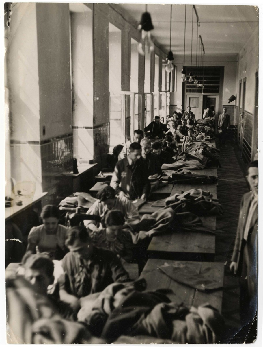 Men and women operating sewing machines work in one of the textile workshops in the Lodz ghetto.