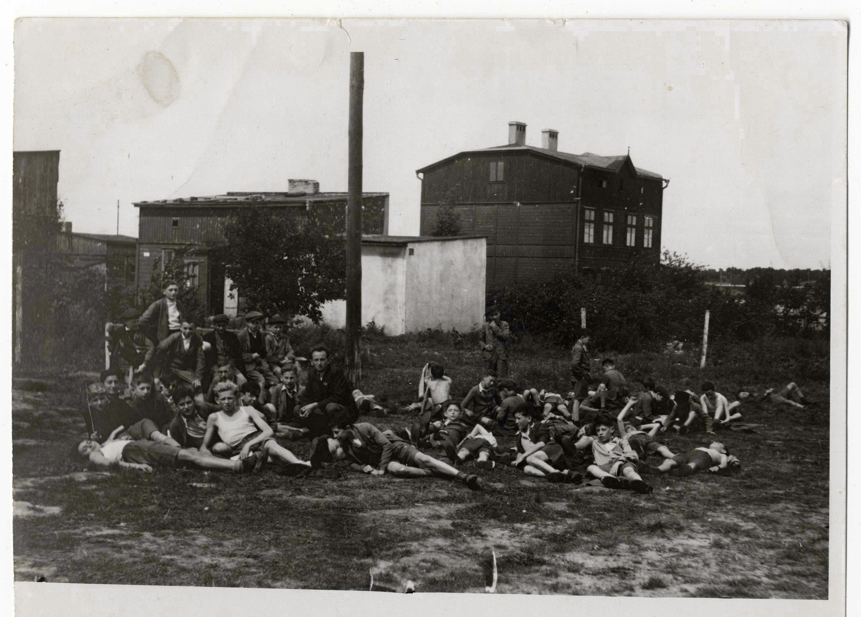 A crowd of children, some wearing athletic clothes, rests in a field in the Marysin colony of the Lodz ghetto.