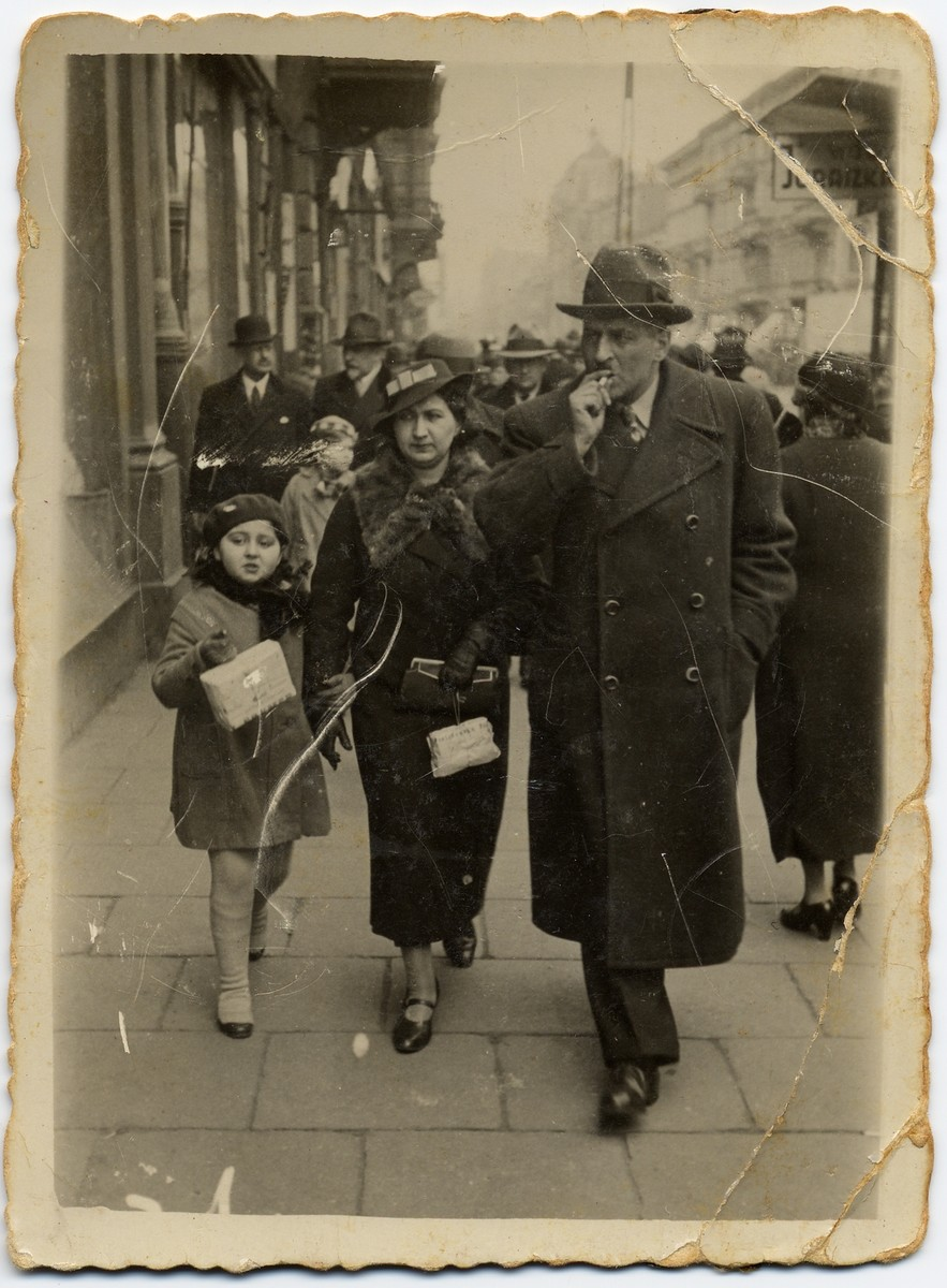 A Jewish family walks down a street in Lodz.
